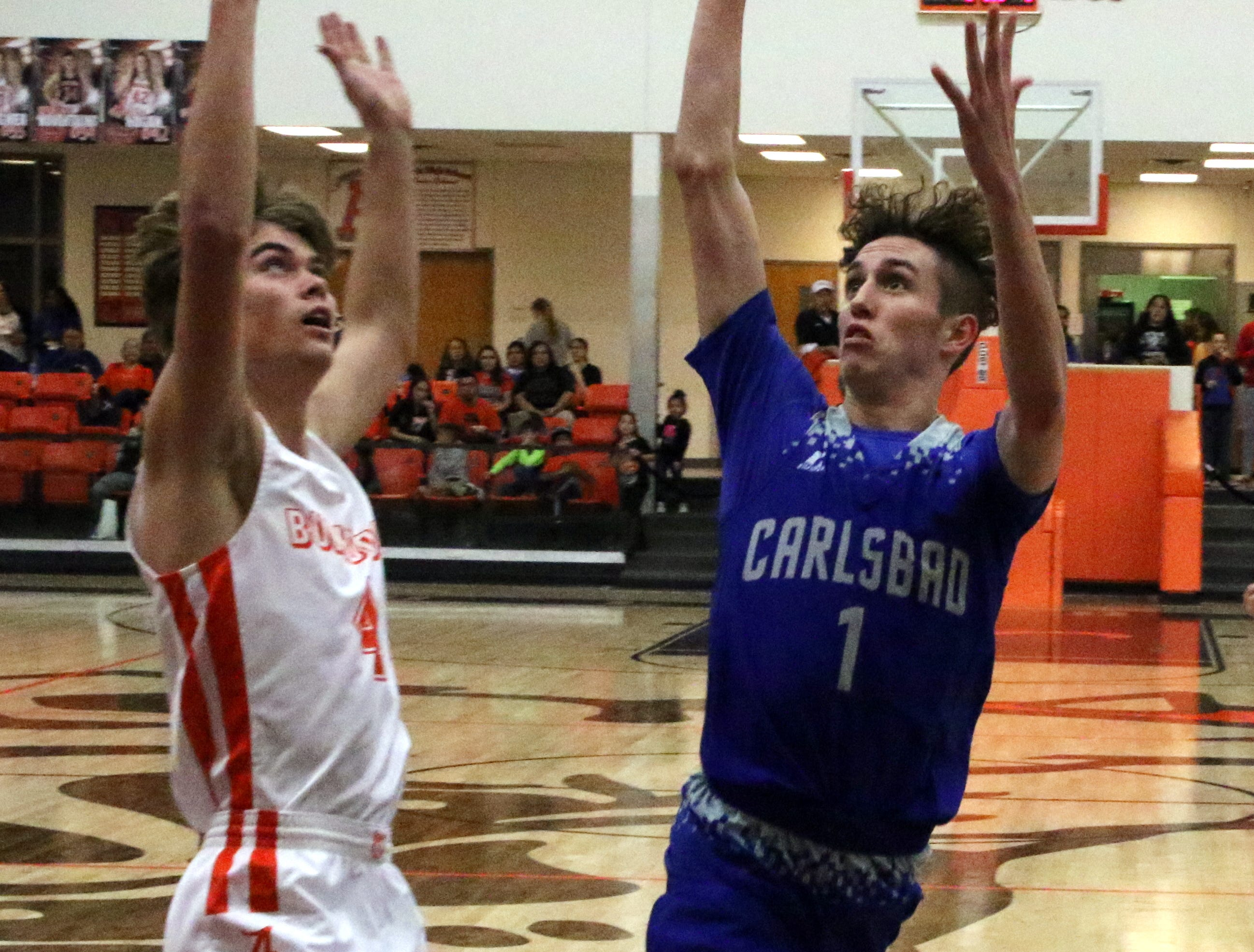 Carlsbad's Josh Sillas takes a contested layup over Artesia's Kale Mauritsen during Friday's game. Carlsbad swept the season series with a 59-56 win.