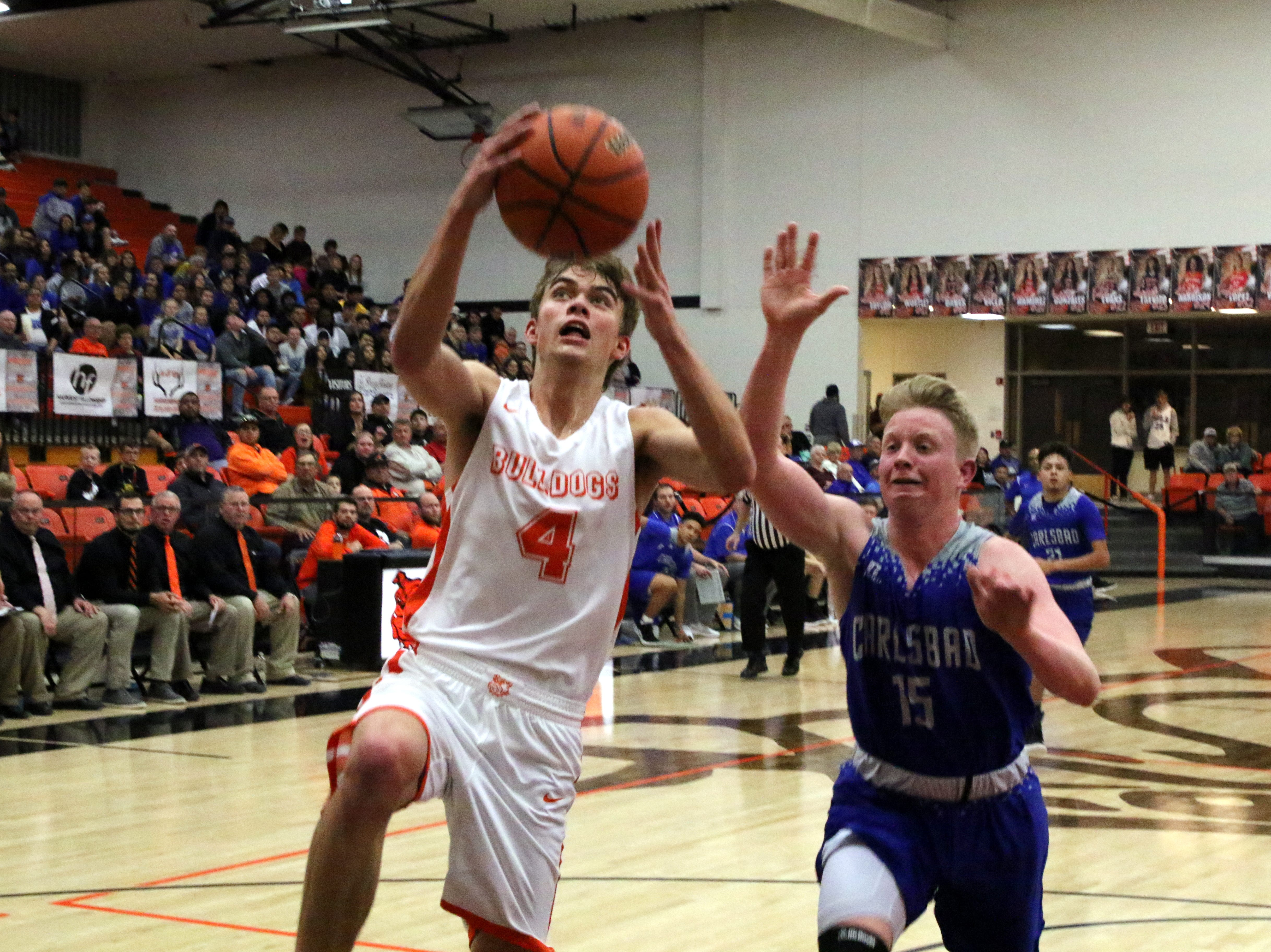 Artesia's Kale Mauritsen goes for a fastbreak layup while Carlsbad's Andrew Miller tries to chase him down during Friday's game.