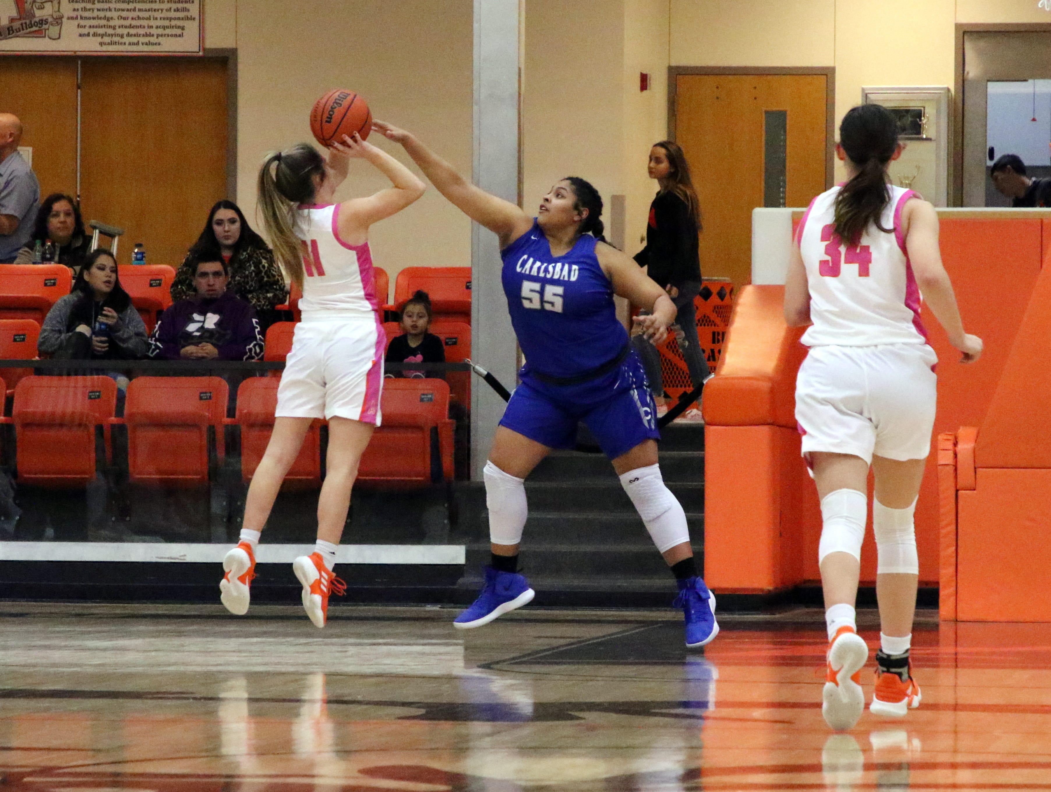 Carlsbad's Kaliyah Montoya (55) goes for a block against Artesia's Makinli Taylor (11) during Friday's game. Taylor finished with eight points and Montoya had one block.