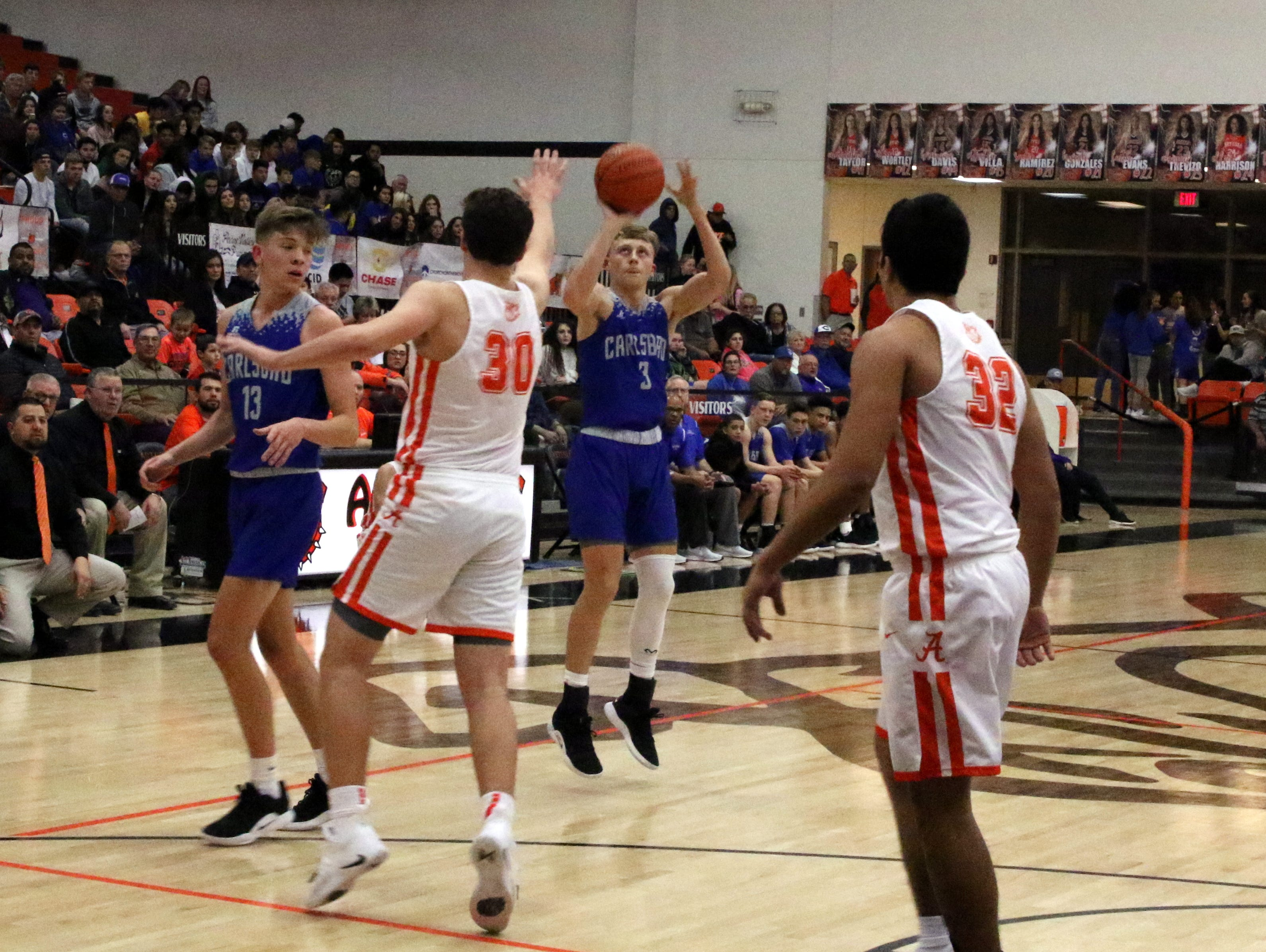 Carlsbad's Riley Hestand take a 3-point shot during Friday's game. He finished with 13 points and Carlsbad swept the season series with a 59-56 win.