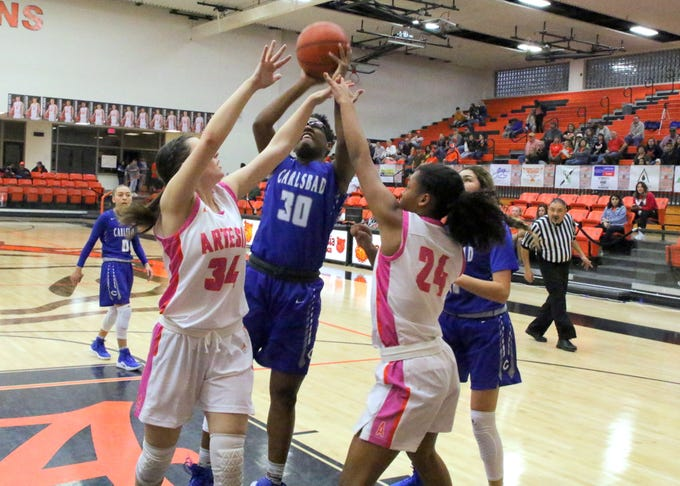 Carlsbad's Dayshaun Moore (30) goes for a contested layup during Friday's game against Artesia. She finished with two points in Carlsbad's 58-35 win.