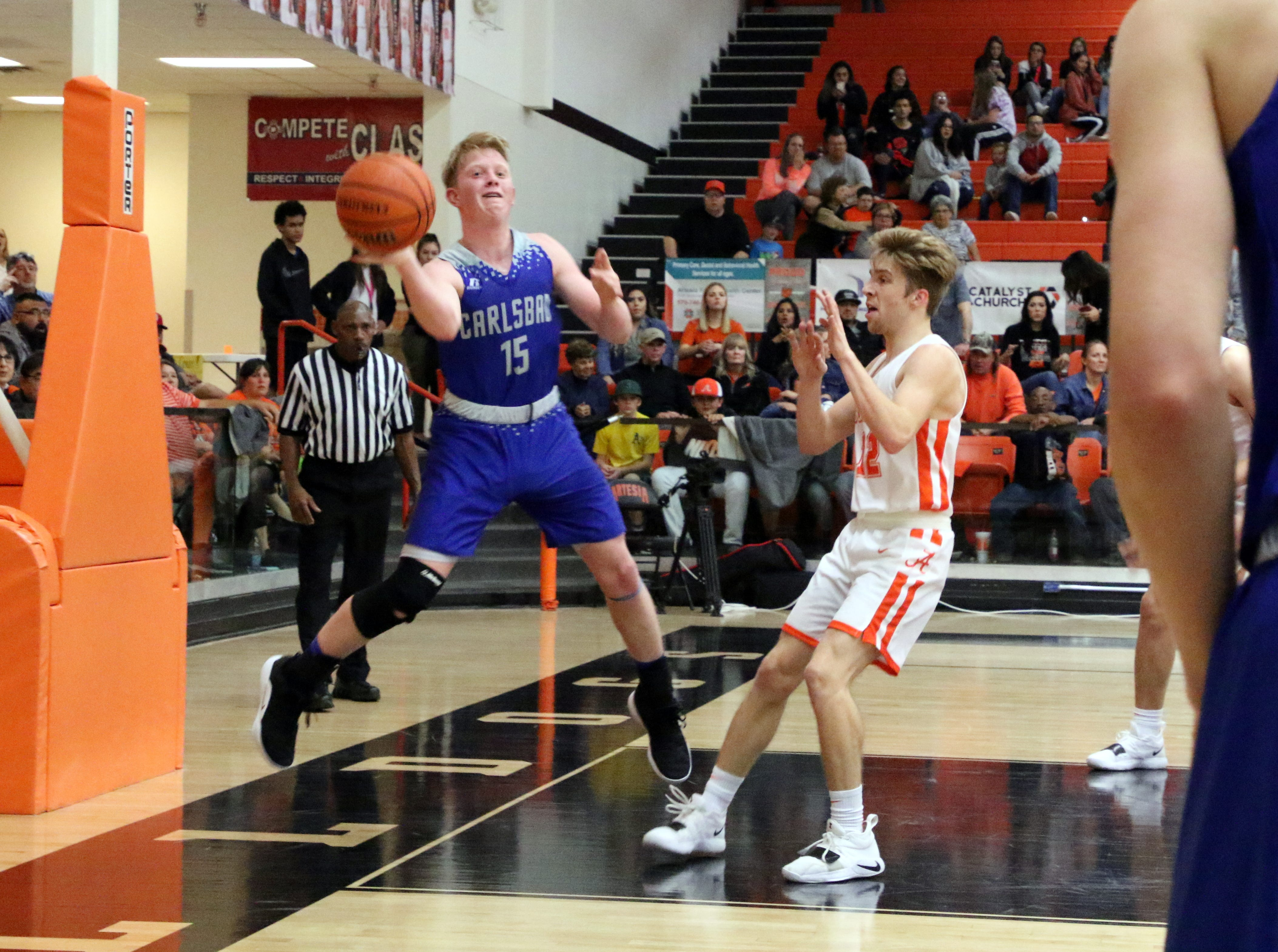 Carlsbad's Andrew Miller saves a ball from going out of bounds during Friday's game against Artesia. Carlsbad swept the season series with a 59-56 win.