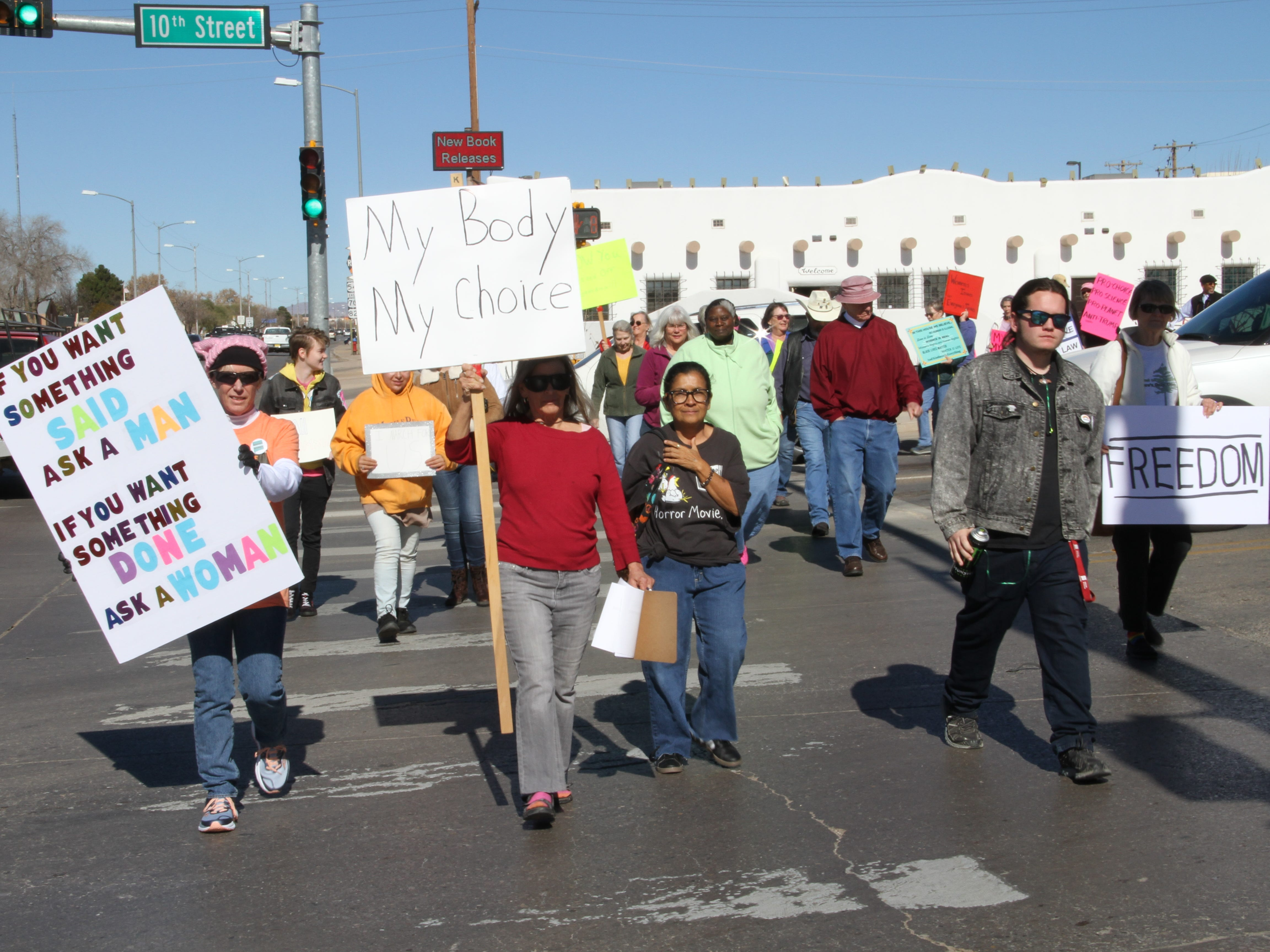 Alamogordo We Trust Women marchers cross 10th Street to Founders Park in solidarity with the national Women's March Saturday.
