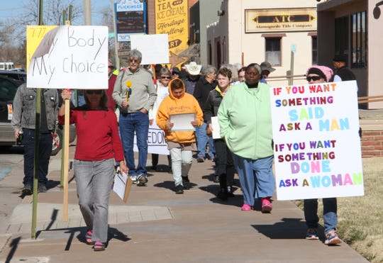 Denise Lang, in red, leads a group of Alamogordo We Trust Women marchers on New York Avenue in solidarity with the national Women's March Saturday.