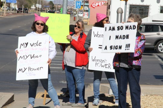 Alamogordo We Trust Women marches display their signs at 10th Street and White Sands Boulevard while marching in solidarity with the national Women's March Saturday.