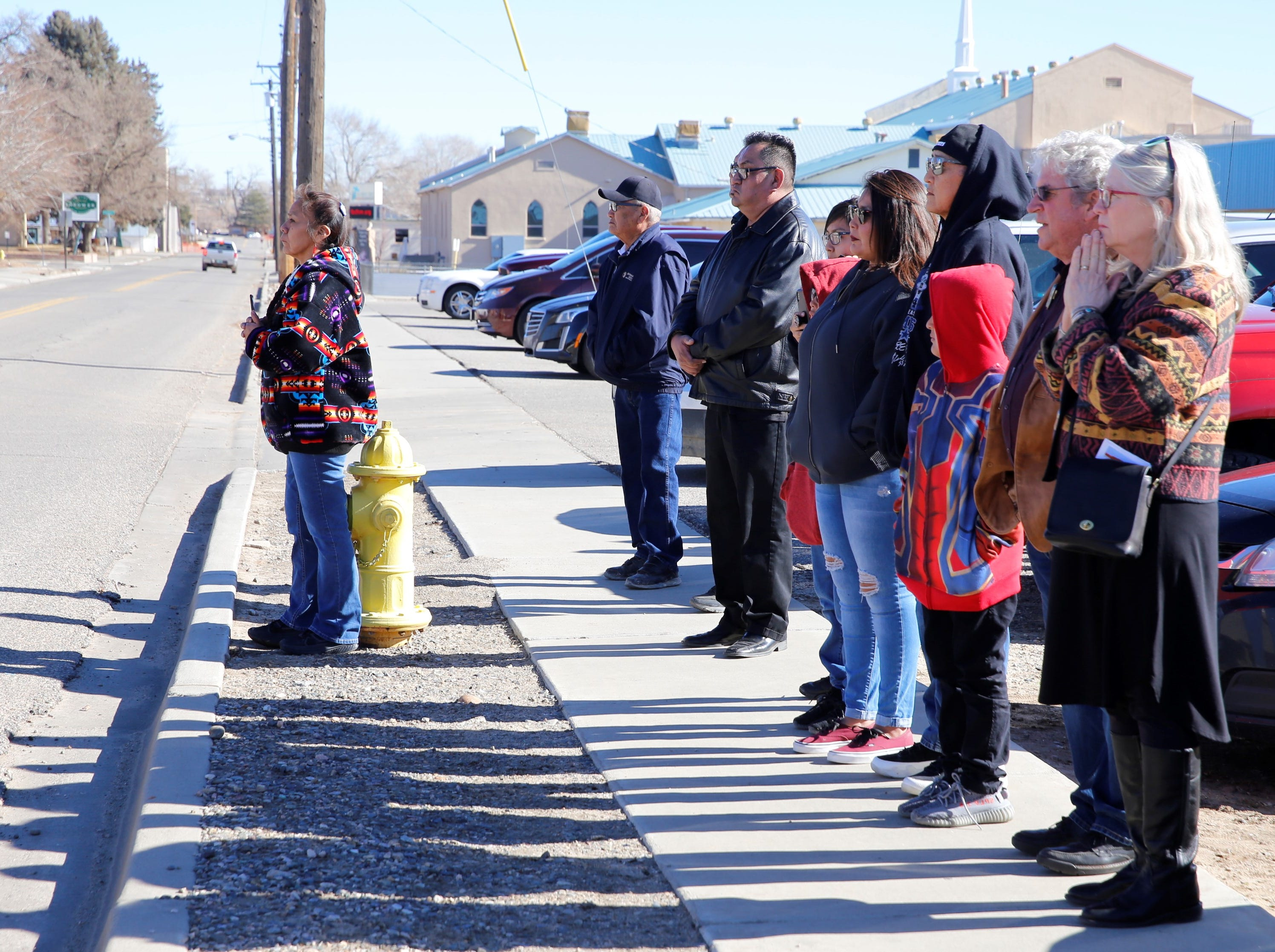 A group watches as the funeral procession for Navajo Code Talker Alfred K. Newman Sr. leave the Maranatha Fellowship Christian Reformed Church on Saturday in Farmington.