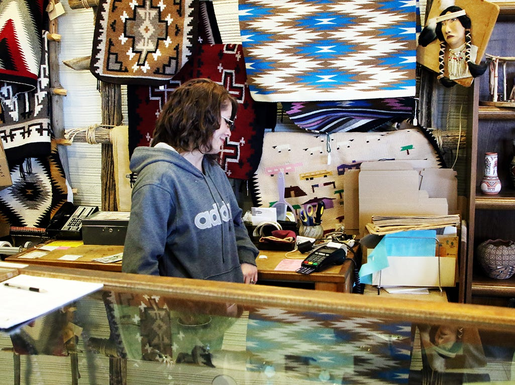Alicia Salazar rings up an admission fee in the Salmon Ruins Muesum gift shop, which has pottery and other items to sell but Saturday saw few customers.