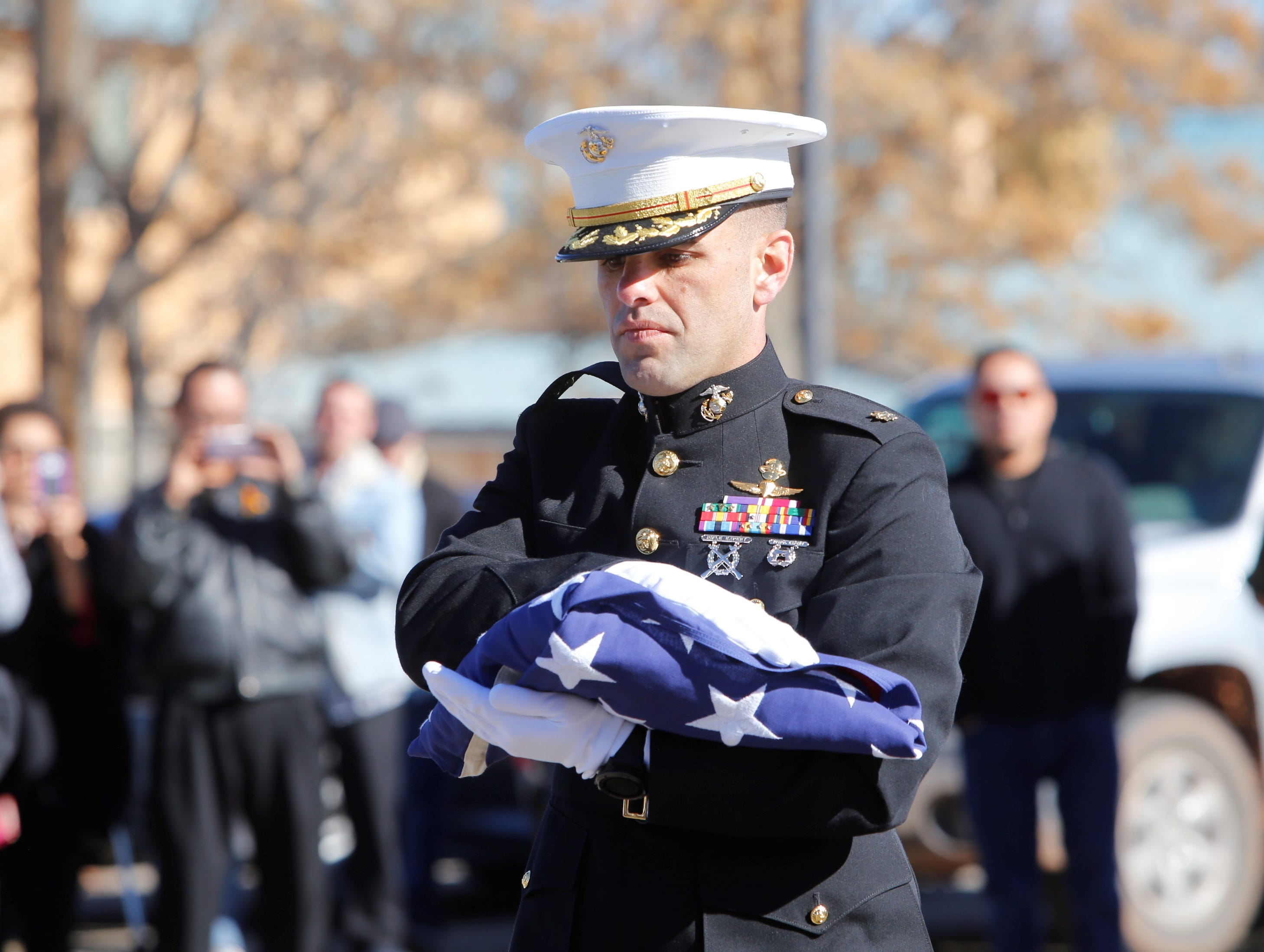 U.S. Marine Corps Maj. Matt Perry prepares to present a flag to the family of Navajo Code Talker Alfred K. Newman Sr. during the funeral service on Saturday in Farmington.