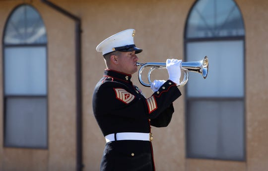 U.S. Marine Corps Gunnery Sgt. Joshua Castaneda plays taps at the funeral service for Navajo Code Talker Alfred K. Newman Sr. on Saturday in Farmington