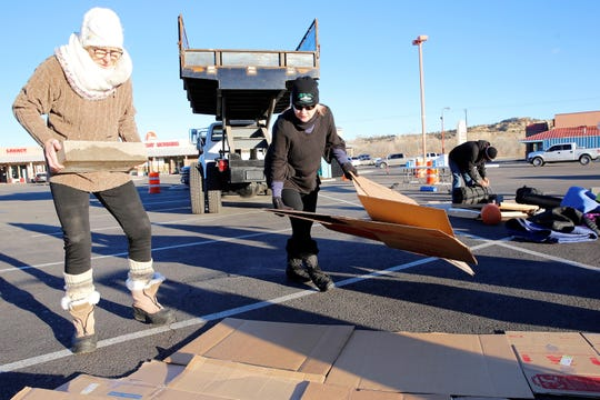 """Beth Loeb, left, and PATH board President Misty Hensley-Munoz lay down cardboard to sleep on during the """"A Night of No Shelter"""" event in the San Juan Plaza parking lot in Farmington on Friday. The event was designed to raise awareness and funds to benefit the local homeless shelter."""