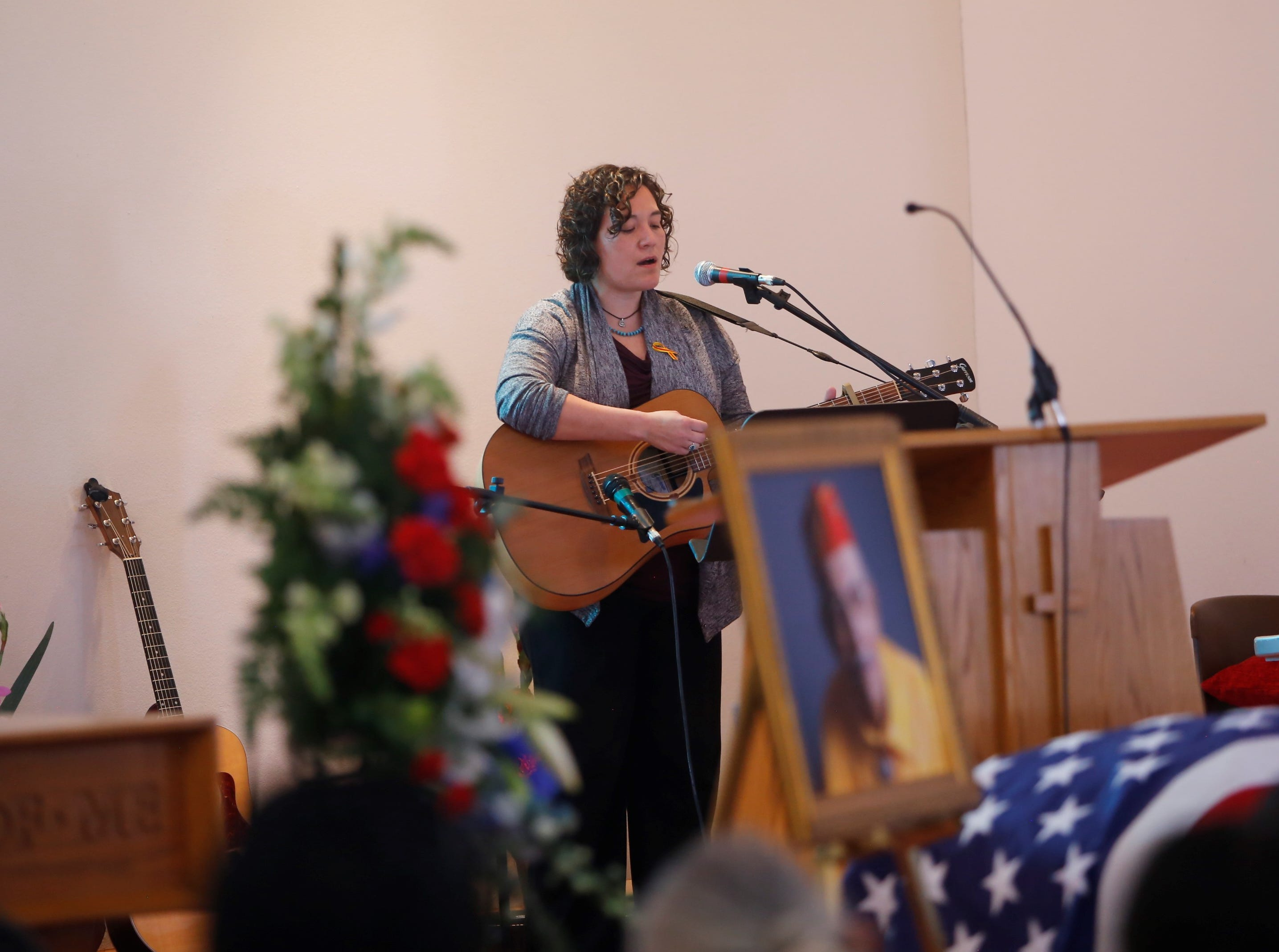Celine Newman sings at her grandfather's funeral service at the Maranatha Fellowship Christian Reformed Church on Saturday in Farmington.