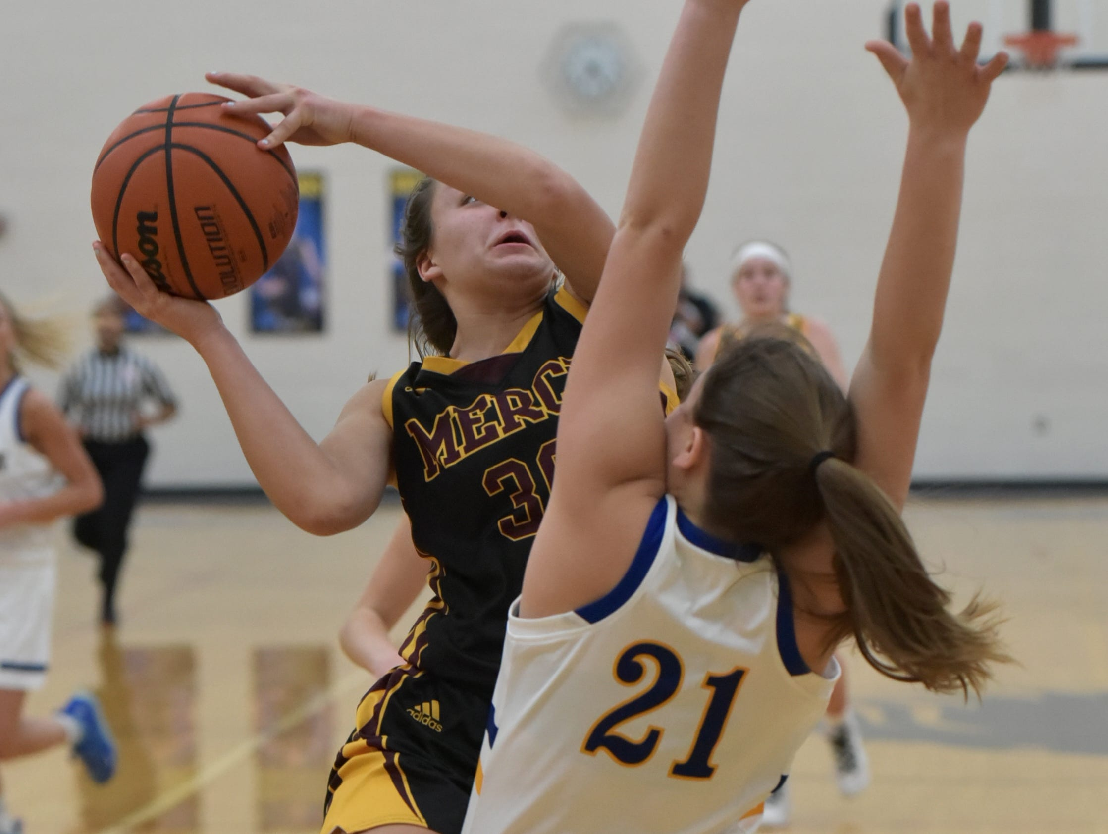 Mercy High's Jill Smith, left, puts up a shot against Marian High's Anna Herberholz during the teams' Jan. 19 match.
