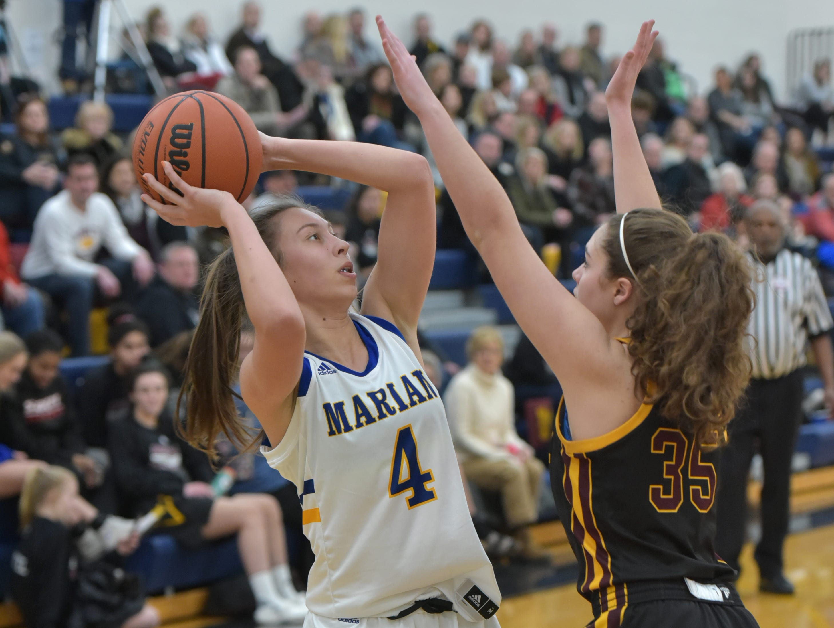 Marian High player Sarah Sylvester, left, feels some pressure from Farmington Mercy's Natalie Ballard.