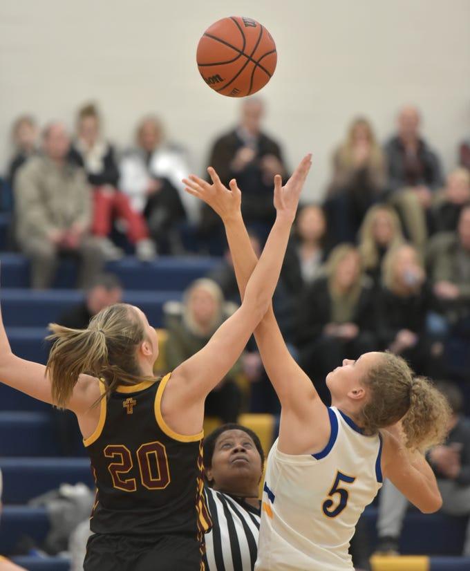 Farmington Mercy's Ellie Tisko, left, and Marian High's Megan Kraus go up for the start-of-the-game jump ball at the start of the Jan. 18 game at Marian High.