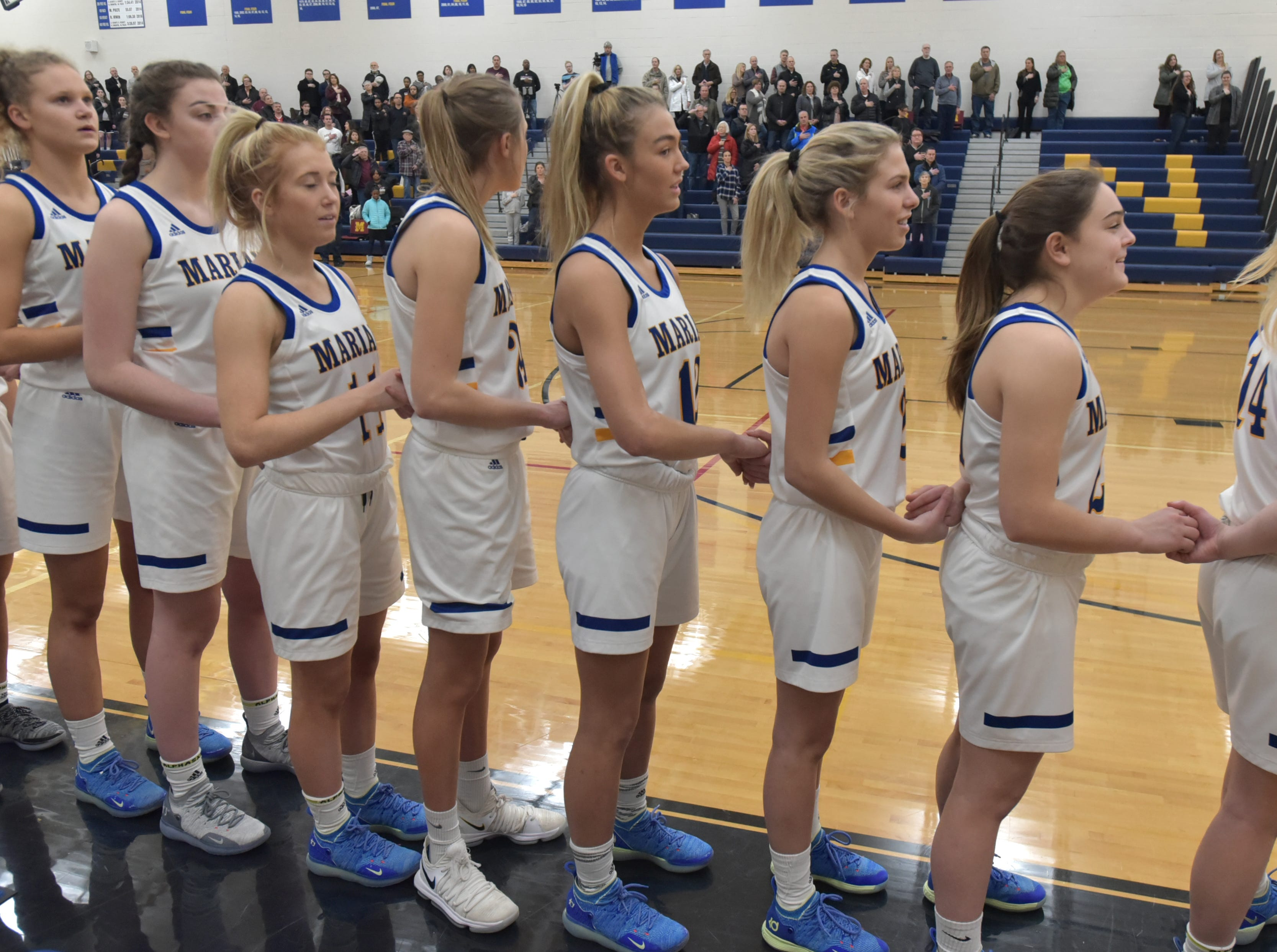The Marian High varisty girls team lines up for the playing of the National Anthem.