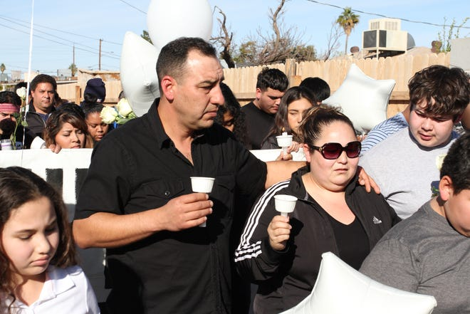 The parents of 14-year-old Antonio Arce walk through the alley where he was shot by a Tempe police officer earlier this week.