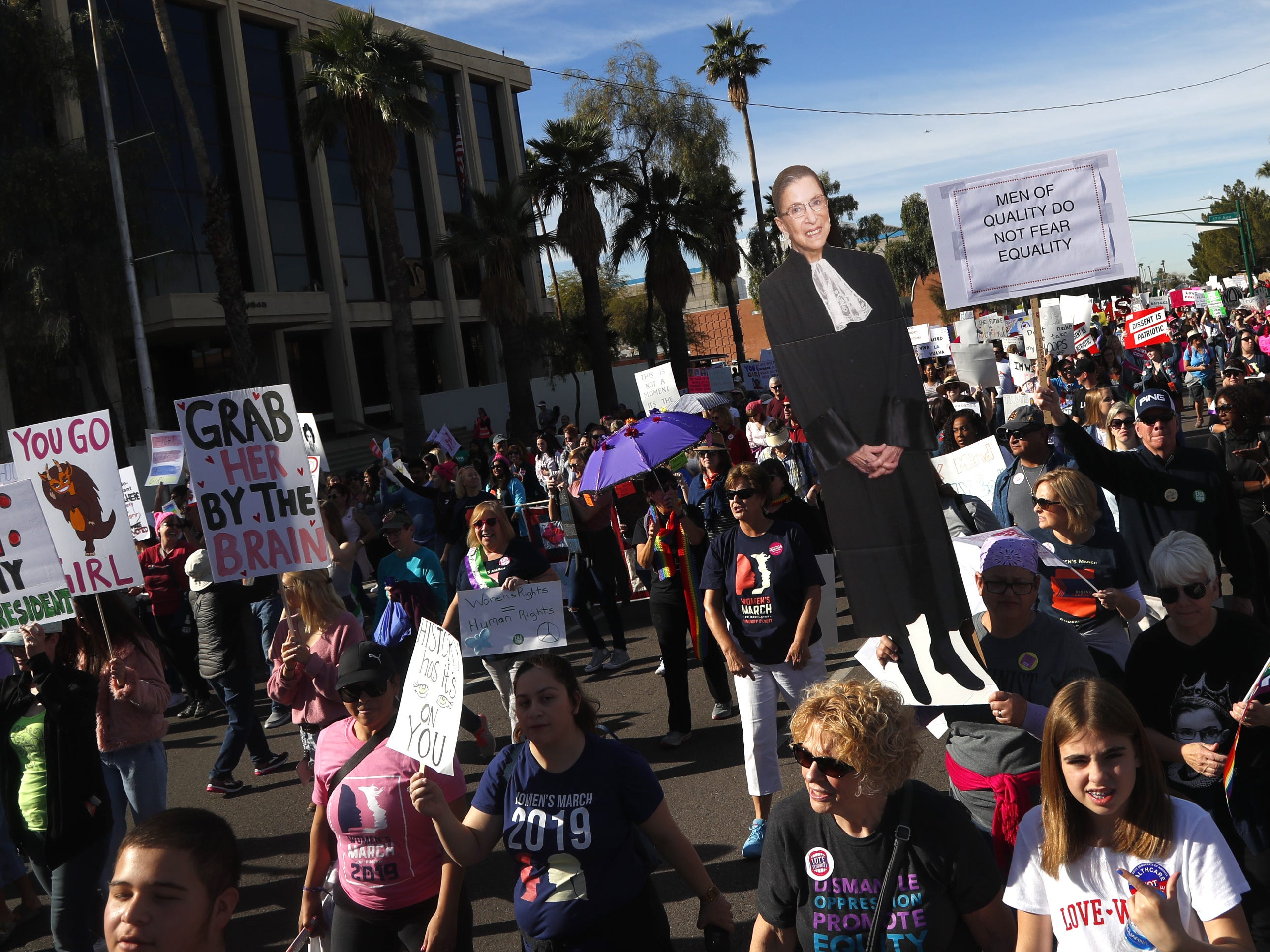 A poster board of Supreme Court Justice Ruth Bader Ginsberg is held by women heading down Jefferson street during the Women's March outside the state capital building in Phoenix, Jan. 19, 2019.