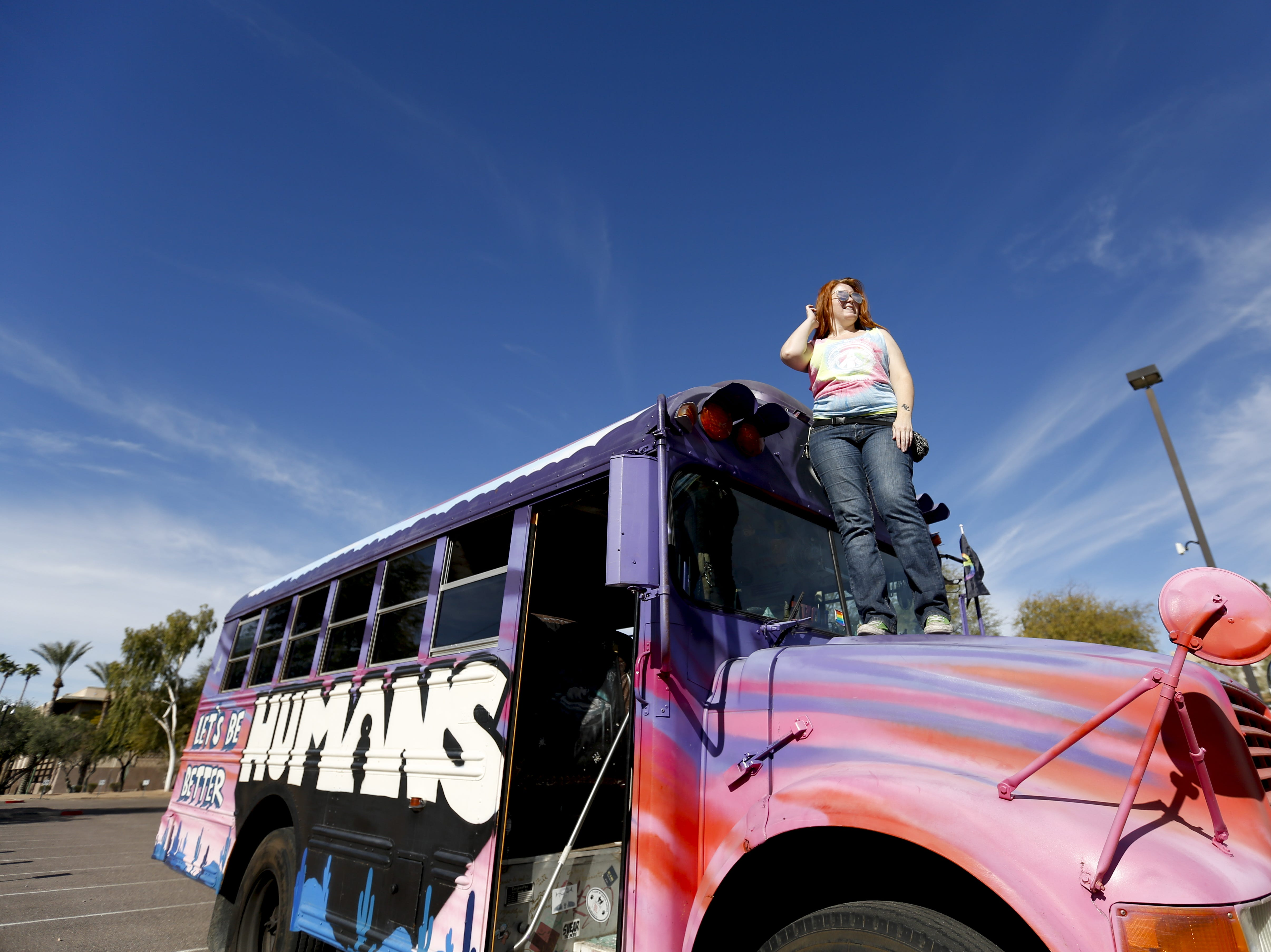 BC Brown, who works with the nonprofit Let's Be Better Humans, invites attendees to sign the inside of the bus at the Phoenix Women's March on Jan. 19, 2019, at the Arizona Capitol.