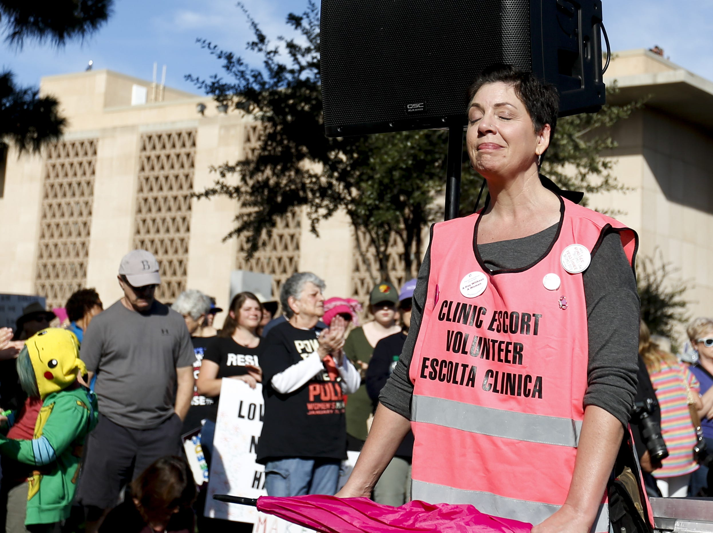 AZ Clinic Defense Force member Tina Nien struggles to hold back tears as the speaker talks about the recent death of a 14-year-old boy during the Phoenix Women's March on Jan. 19, 2019, at the Arizona Capitol.