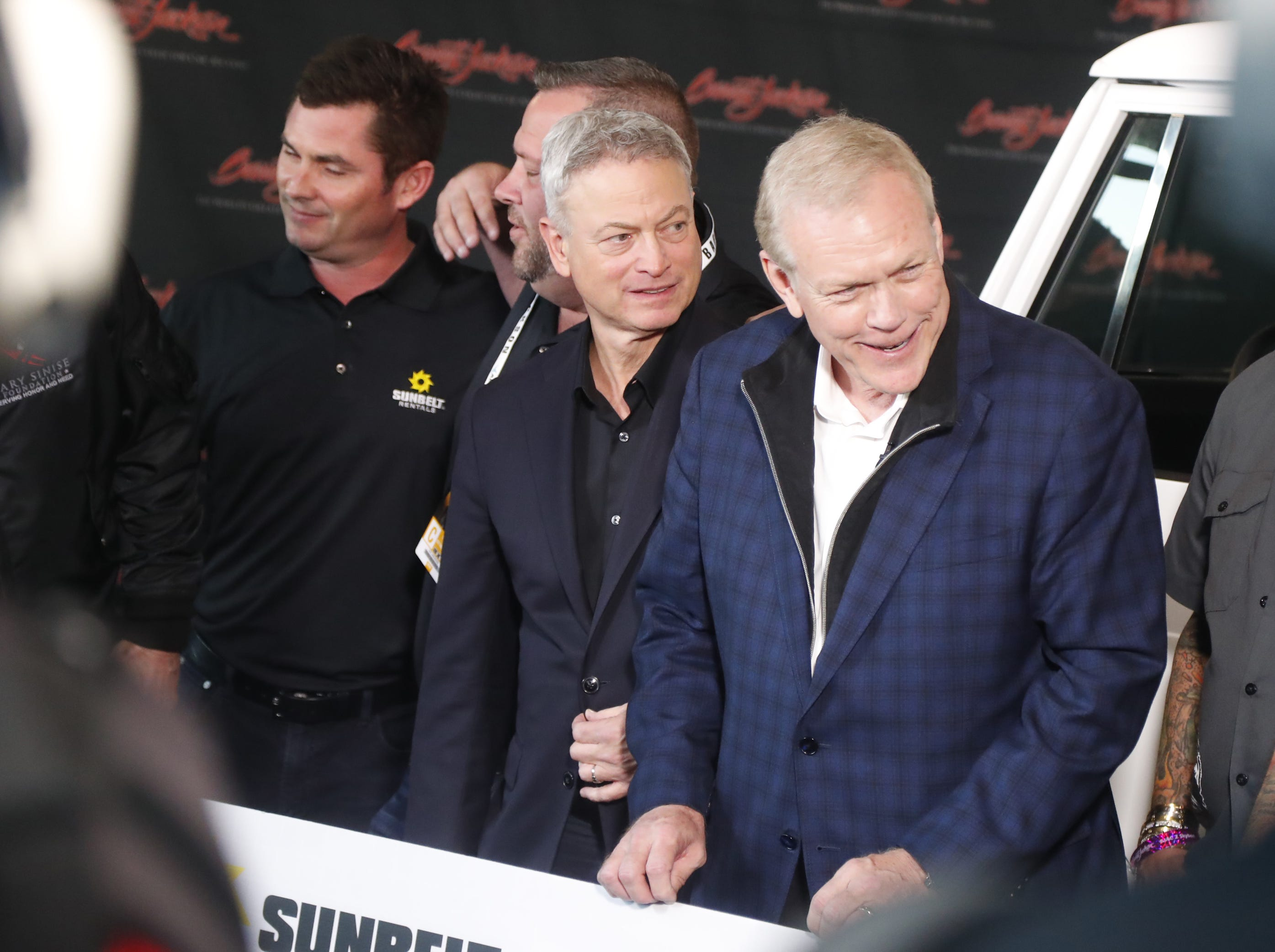 Gary Sinise stands next to Craig Jackson, CEO and chairman of Barrett-Jackson, as people take pictures at the Barrett-Jackson collector-car auction at WestWorld in Scottsdale on Jan. 18, 2019.