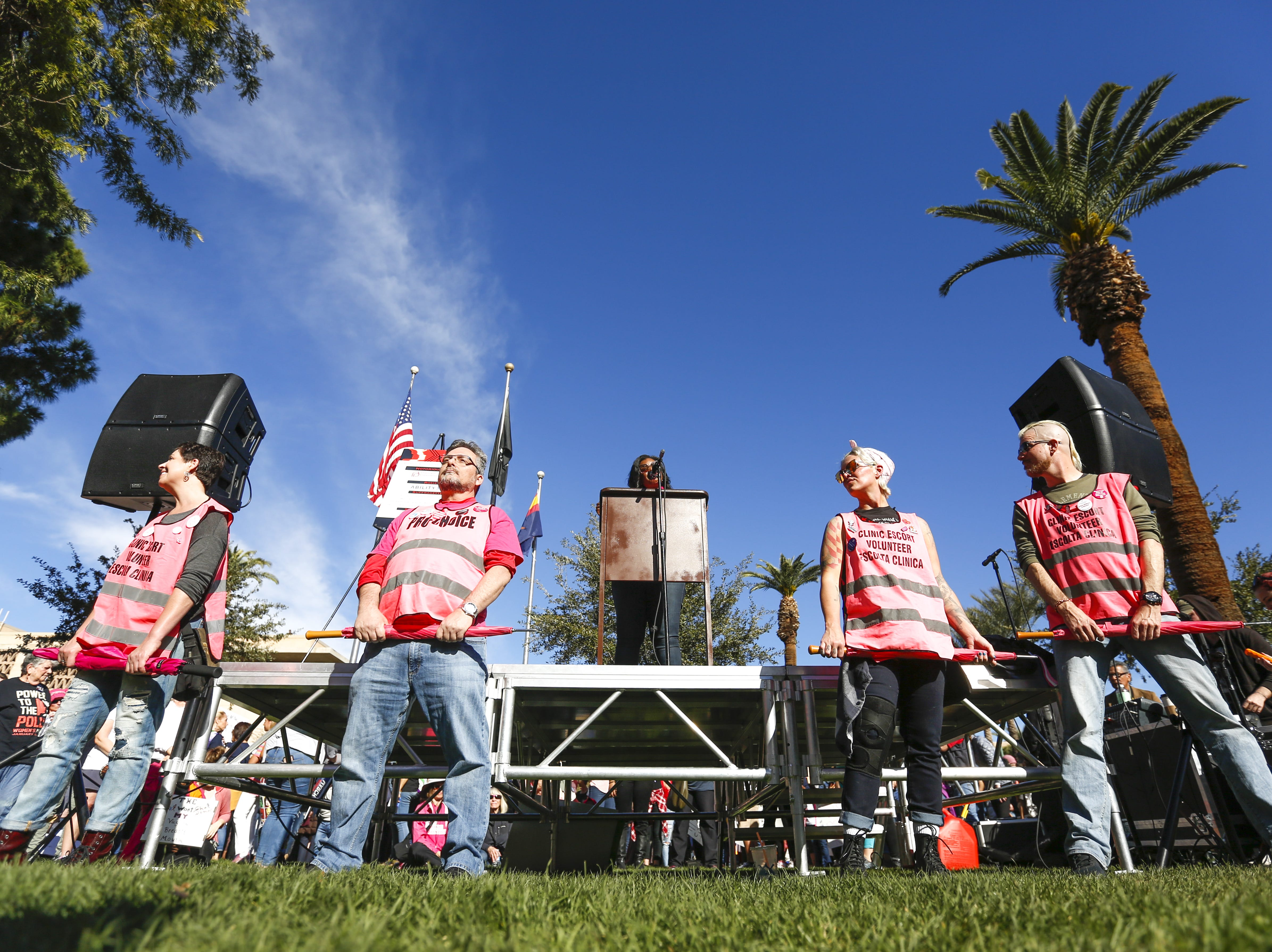 AZ Clinic Defense Force members (from left to right) Tina Nien Stan Tierney, Sarah Henry and Dean Robitaille stand between the stage and the crowd at the Phoenix Women's March on Jan. 19, 2019, at the Arizona Capitol. The AZ Clinic Defense Force escorts women to appointments when they may face protestors, such as outside of Planned Parenthood facilities.