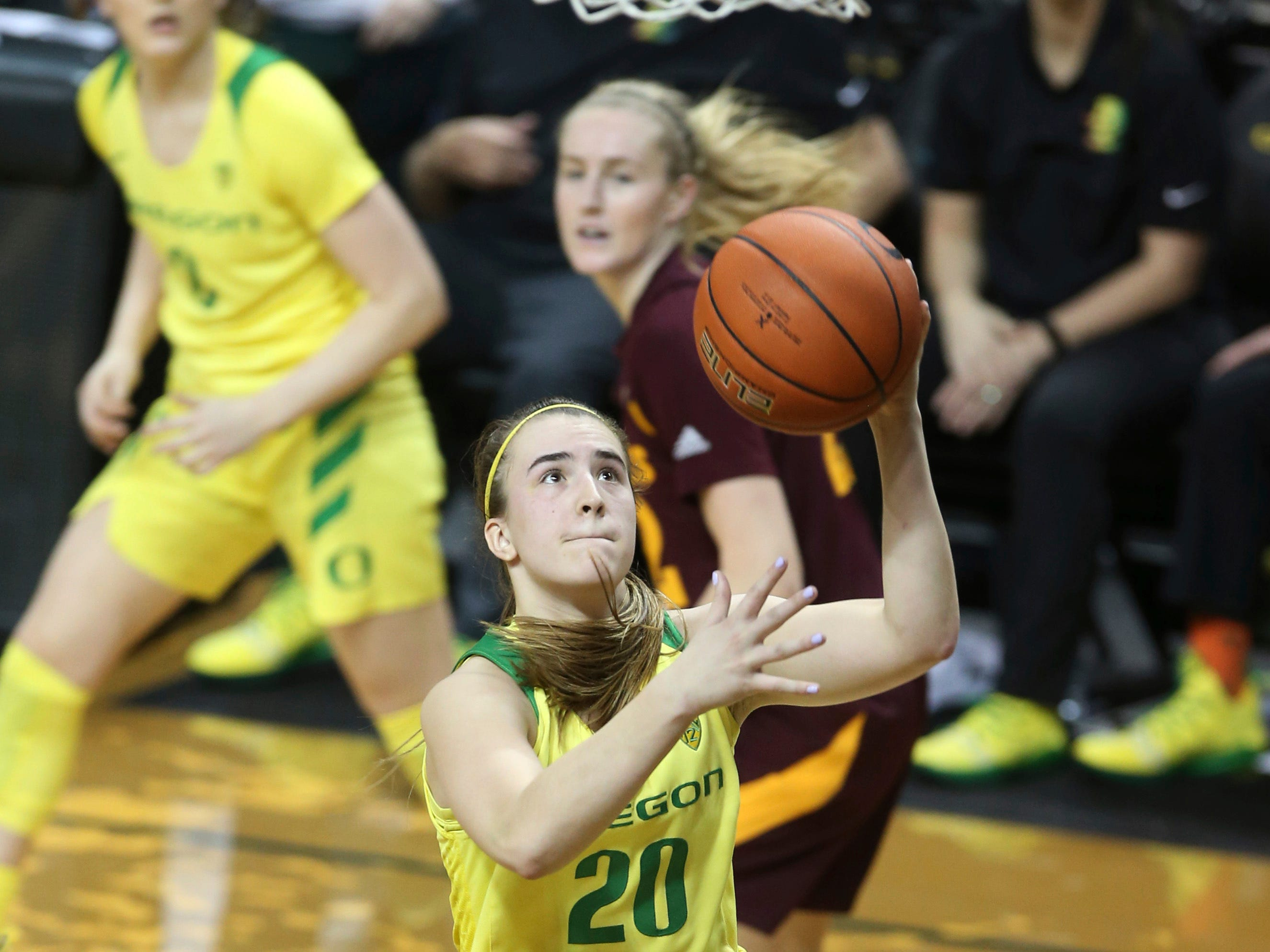 Oregon's Sabrina Ionescu, center, goes up for a shot ahead of teammate Taylor Chavez, left, and Arizona State's Courtney Ekmark during the fourth quarter of an NCAA college basketball game Friday, Jan 18, 2019, in Eugene, Ore. (AP Photo/Chris Pietsch)
