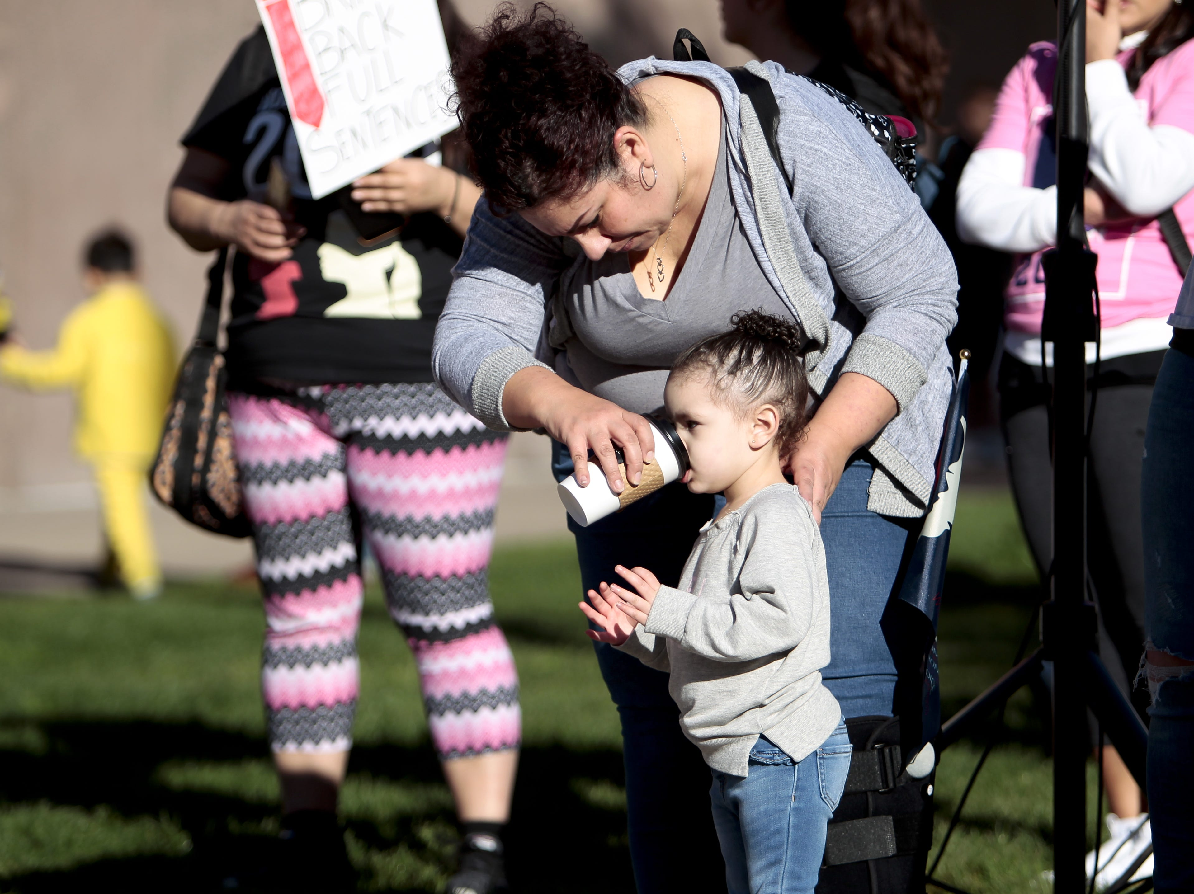 Lotami Tomas gives her granddaughter 1-year-old Messia Brisby a sip of her drink at the Phoenix Women's March on Jan. 19, 2019, at the Arizona Capitol.