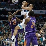 Charlotte Hornets' Miles Bridges, center, drives between Phoenix Suns' Josh Jackson (20) and Richaun Holmes (21) during the first half of an NBA basketball game in Charlotte, N.C., Saturday, Jan. 19, 2019. (AP Photo/Chuck Burton)
