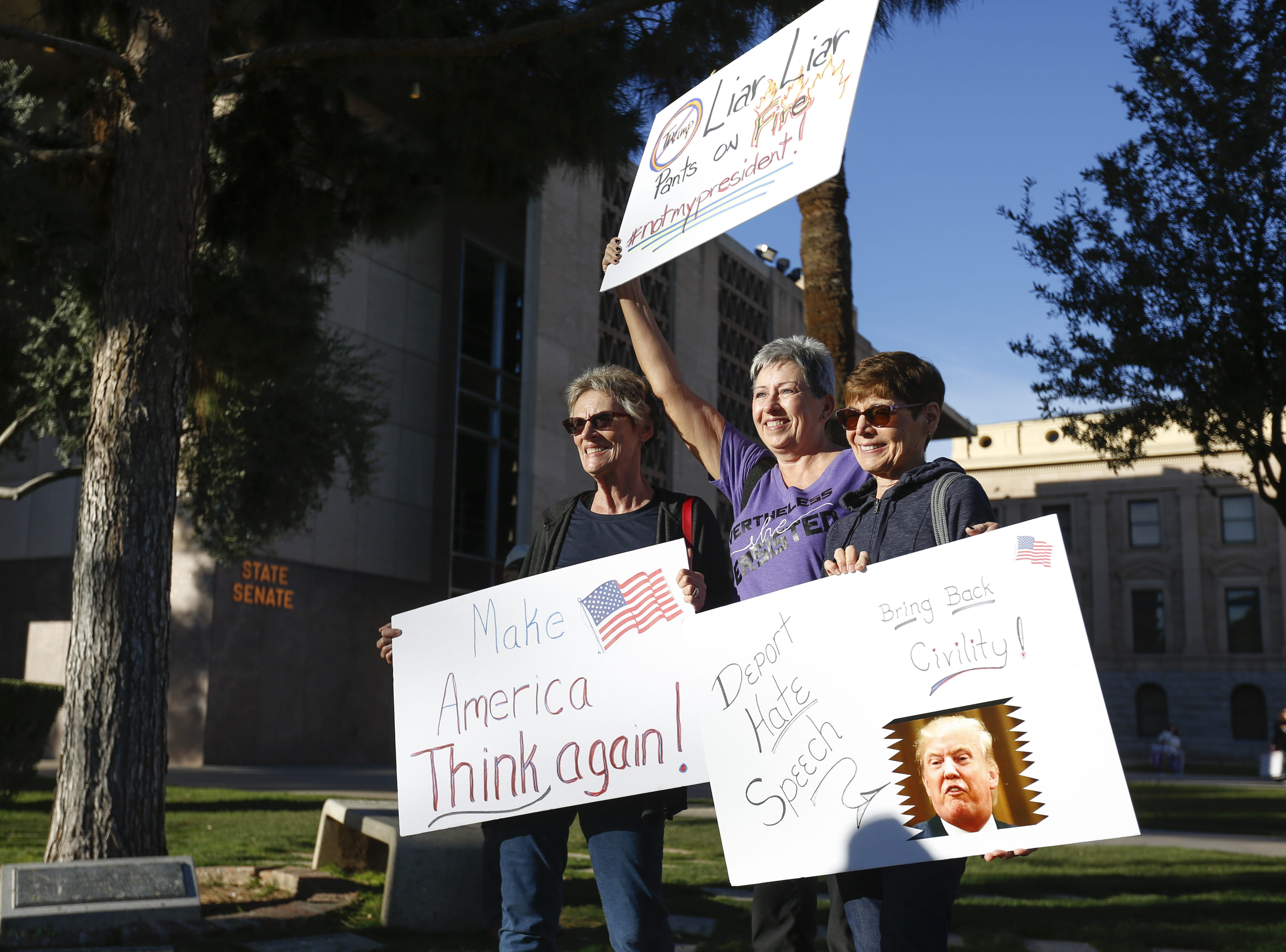 From left: Kathy Collison, Carla Llewellyn and Louise Honike take a photo together with their signs at the Phoenix Women's March on Jan. 19, 2019, at the Arizona Capitol.