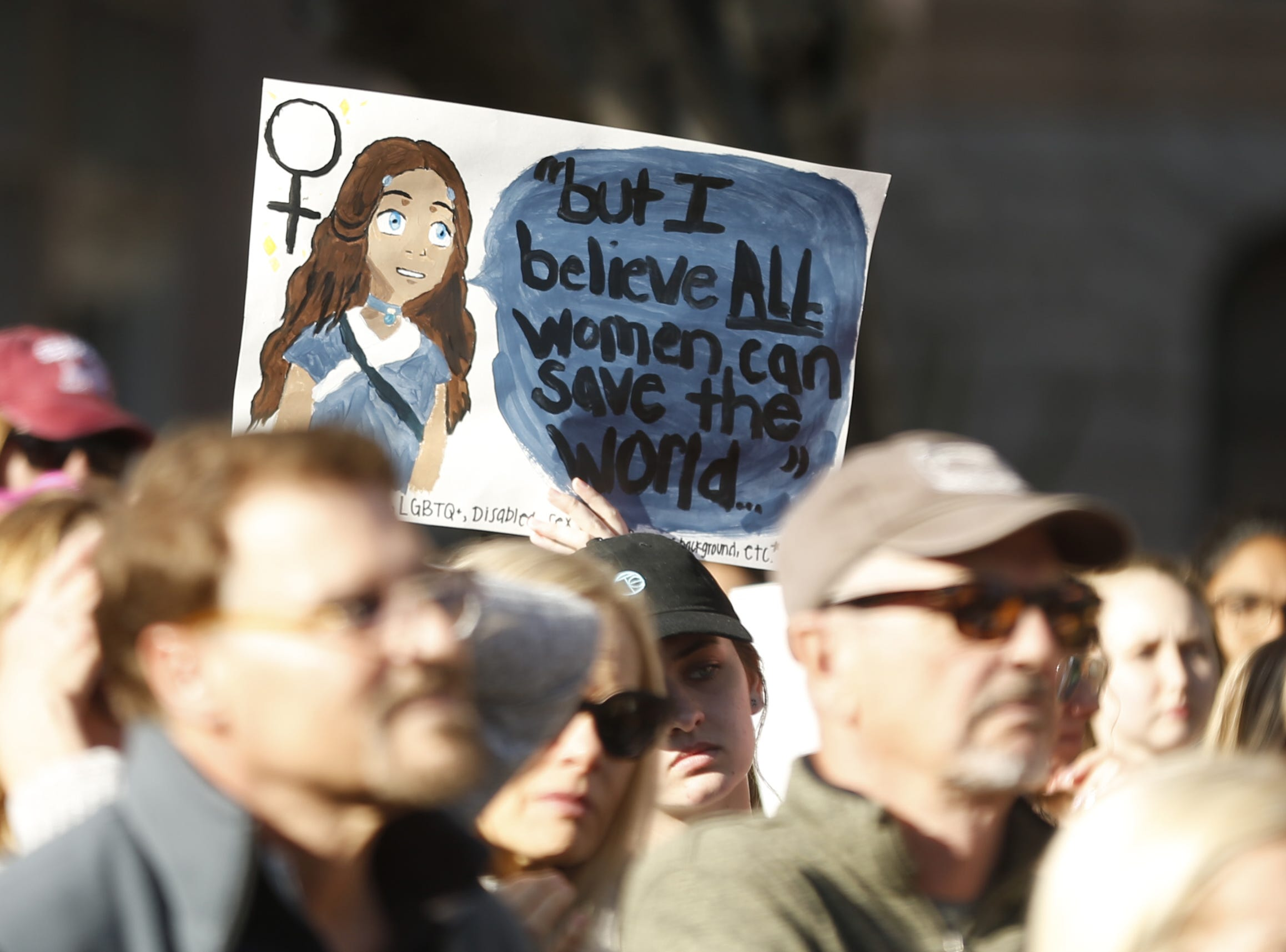 Women hold signs up supporting the Women's March outside the Arizona Capitol in Phoenix, Jan. 19, 2019.