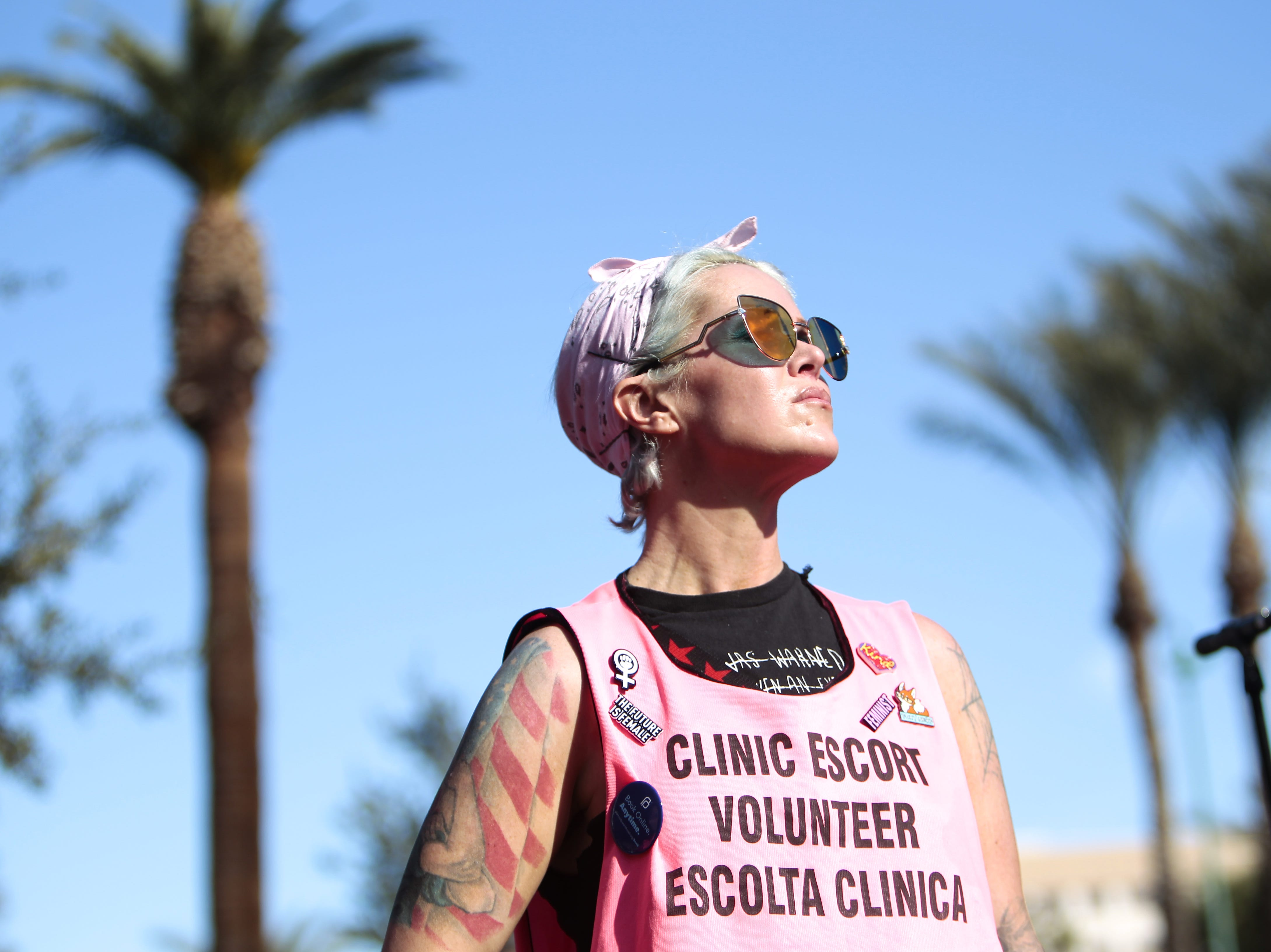 Sarah Henry, a clinic escort volunteer with the AZ Clinic Escort Force, stands between the stage and the crowd at the Phoenix Women's March on Jan. 19, 2019, at the Arizona Capitol.