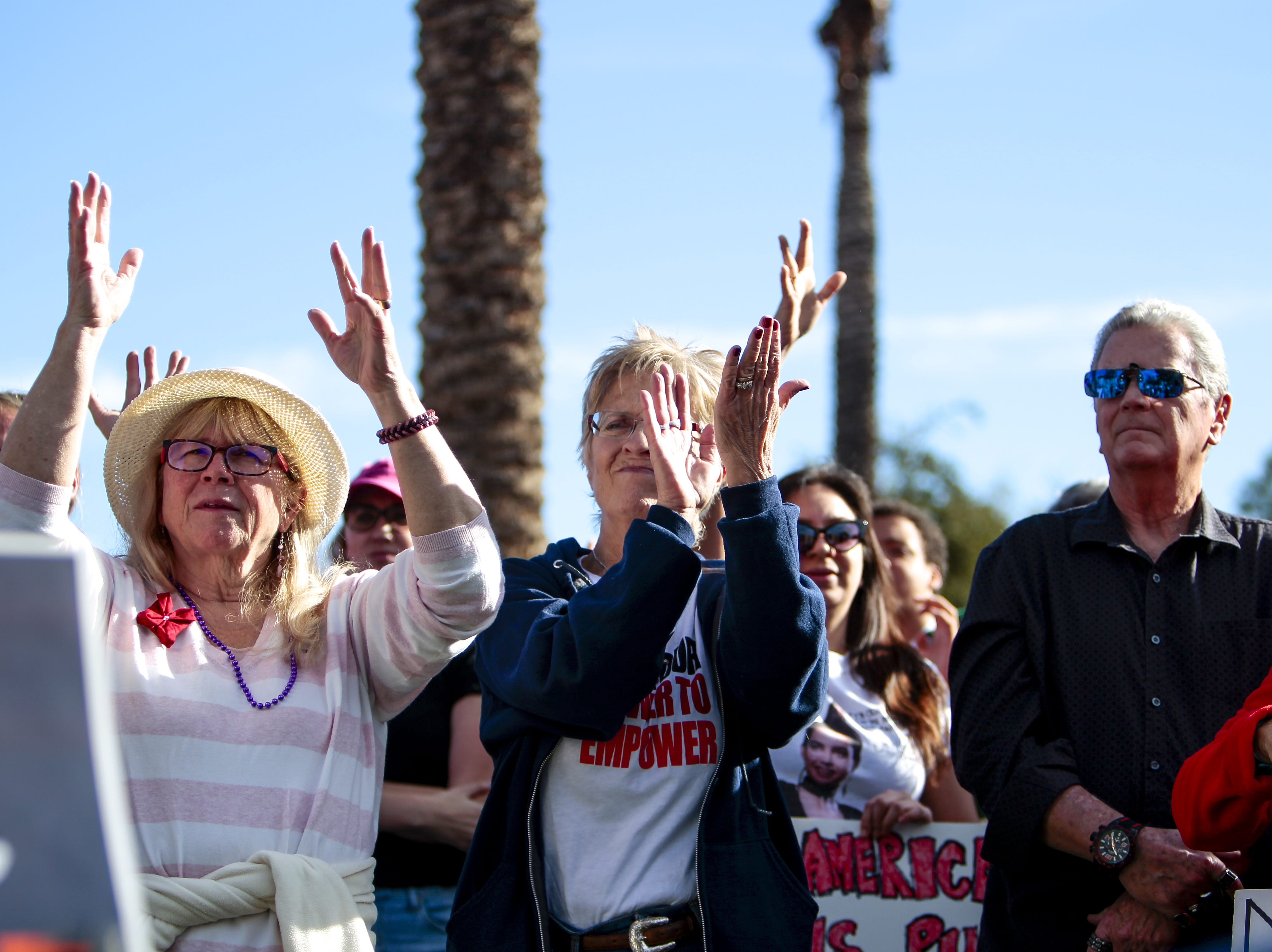 The crowd cheers in sign language during Sherri Collins' speech about the difficulties women with disabilities face at the Phoenix Women's March on Jan. 19, 2019, at the Arizona Capitol.