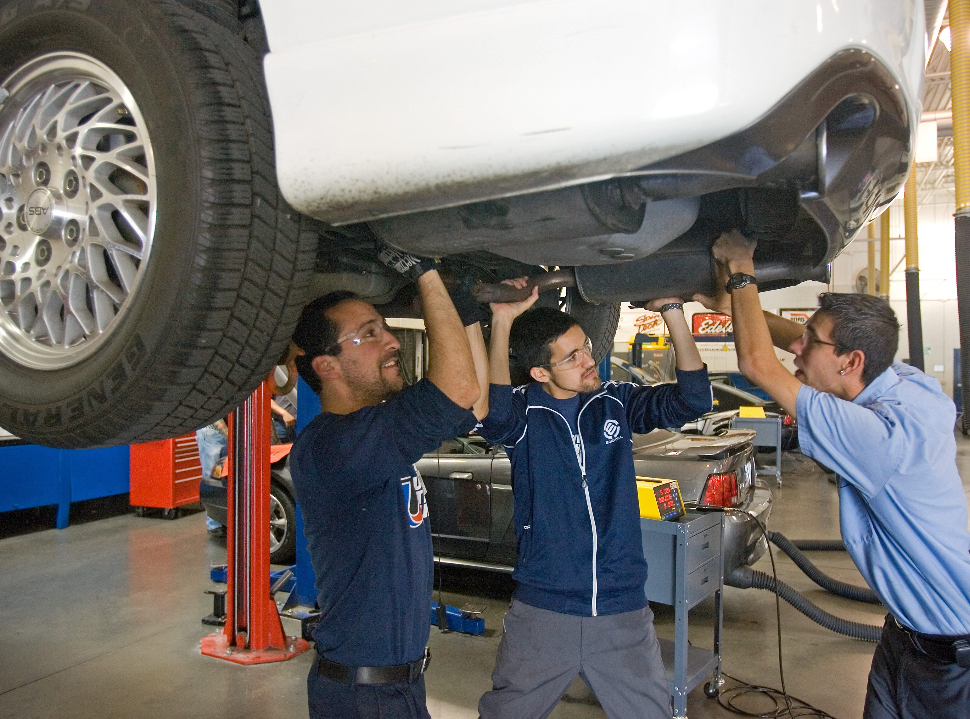 Students Moses Gonzales, Rick Carrera and Jose Becerra remove a muffler during a class at the Universal Technical Institute in April 2008.