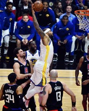 Golden State Warriors center DeMarcus Cousins hangs in the air on his way to a one-handed slam dunk in the first quarter against the Los Angeles Clippers at Staples Center.