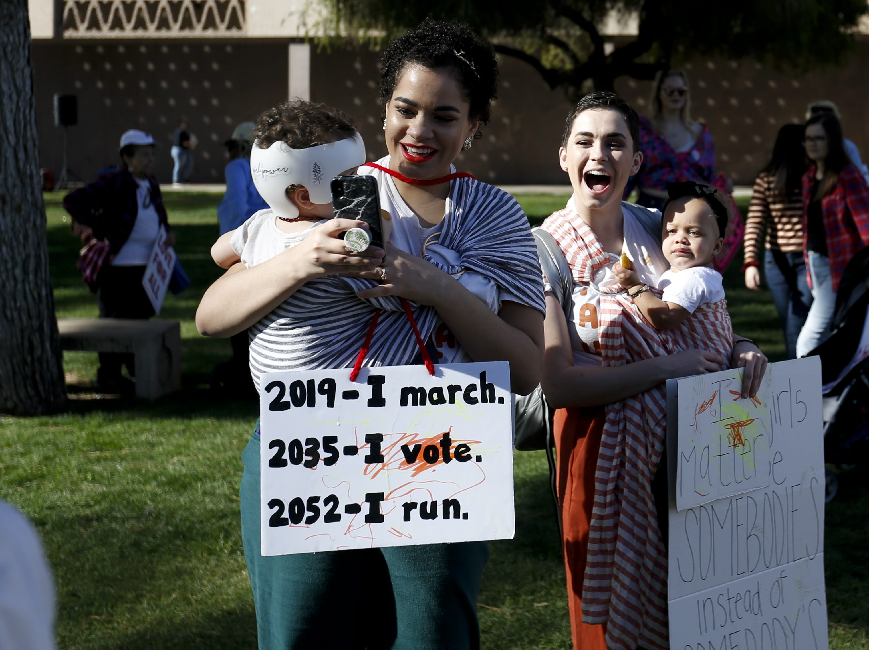 Sydney Muller (left) takes a photo of another Women's March attendee as she holds her daughter Georgia Muller, 1, on Jan. 19, 2019, at the Arizona Capitol.