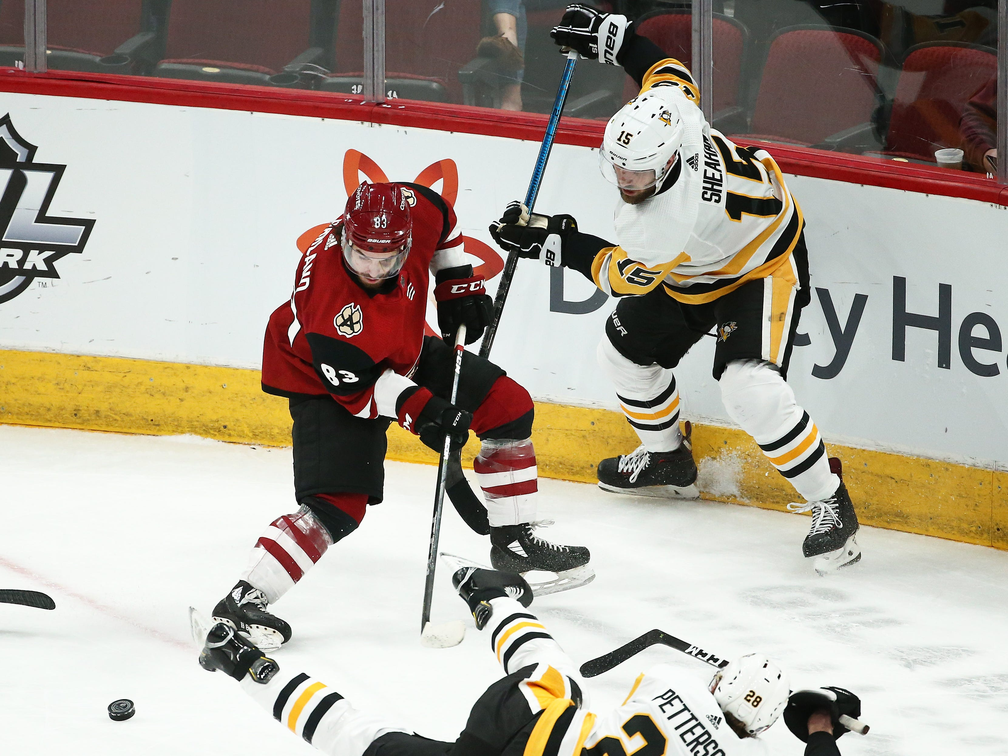 Arizona Coyotes' Conor Garland battles for the puck with Pittsburgh Penguins Marcus Pettersson (28) and Riley Sheahan (15) in the first period on Jan. 18 at Gila River Arena.