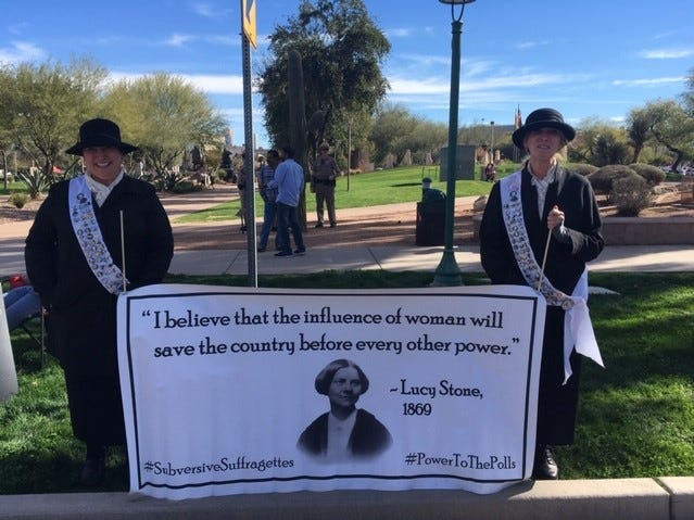 Sisters Paula (left) Baily of North Carolina, and Elizabeth Baily of Phoenix, wear suffragette outfits and buttons as they participate the Women's March in Phoenix, Jan. 19, 2019.
