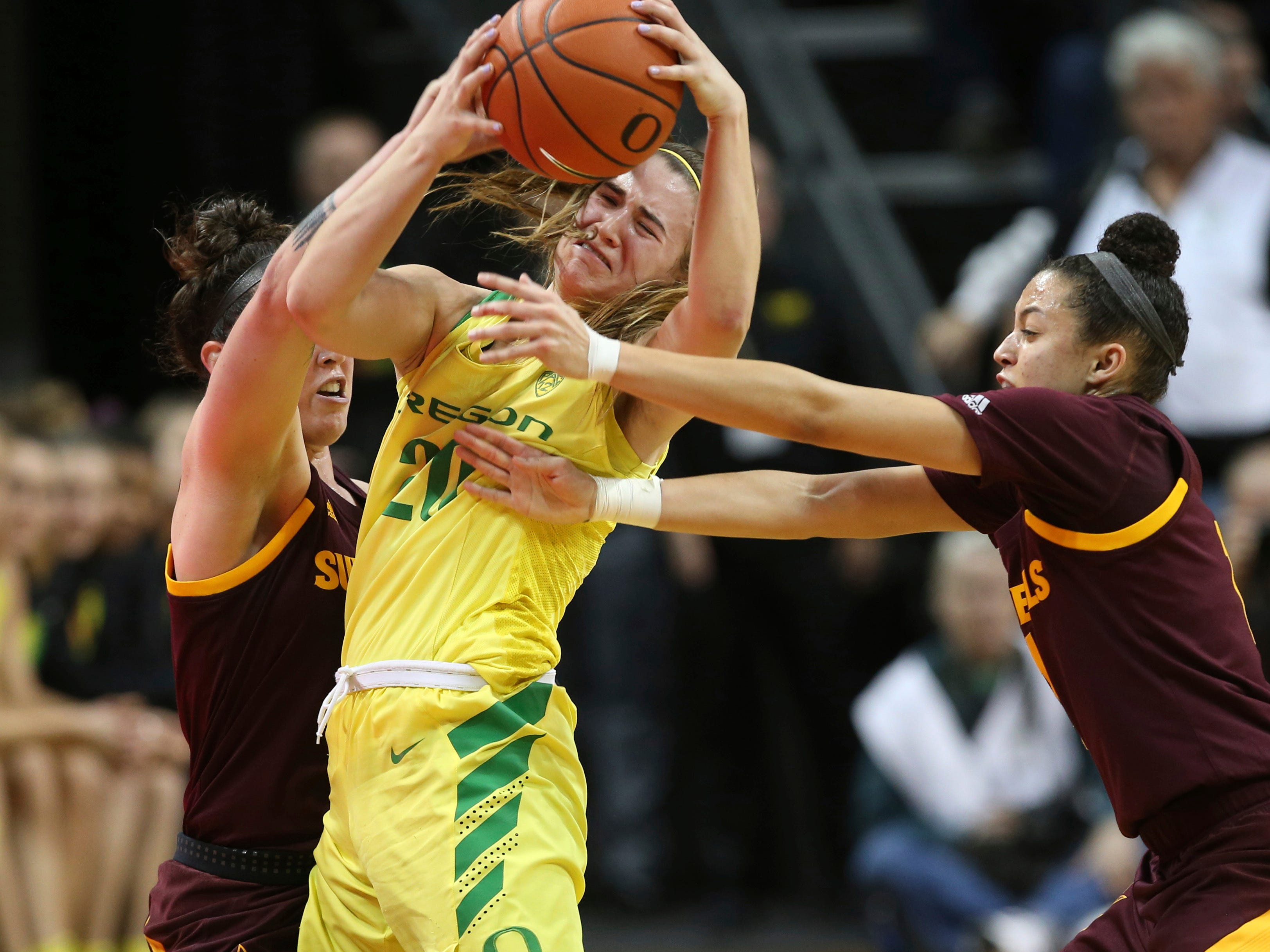 Arizona State's Robbi Ryan, left, and Reili Richardson, right, defend against Oregon's Sabrina Ionescu near the end of an NCAA college basketball game Friday, Jan 18, 2019, in Eugene, Ore. Ionescu was fouled on the play. (AP Photo/Chris Pietsch)