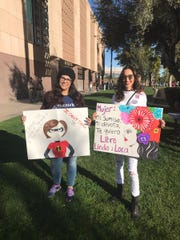Cynthia Rodriguez (left) and Eddi Treviso  share their signs at the Phoenix Women's March 2019 at the Arizona Capitol, Jan. 19, 2019.