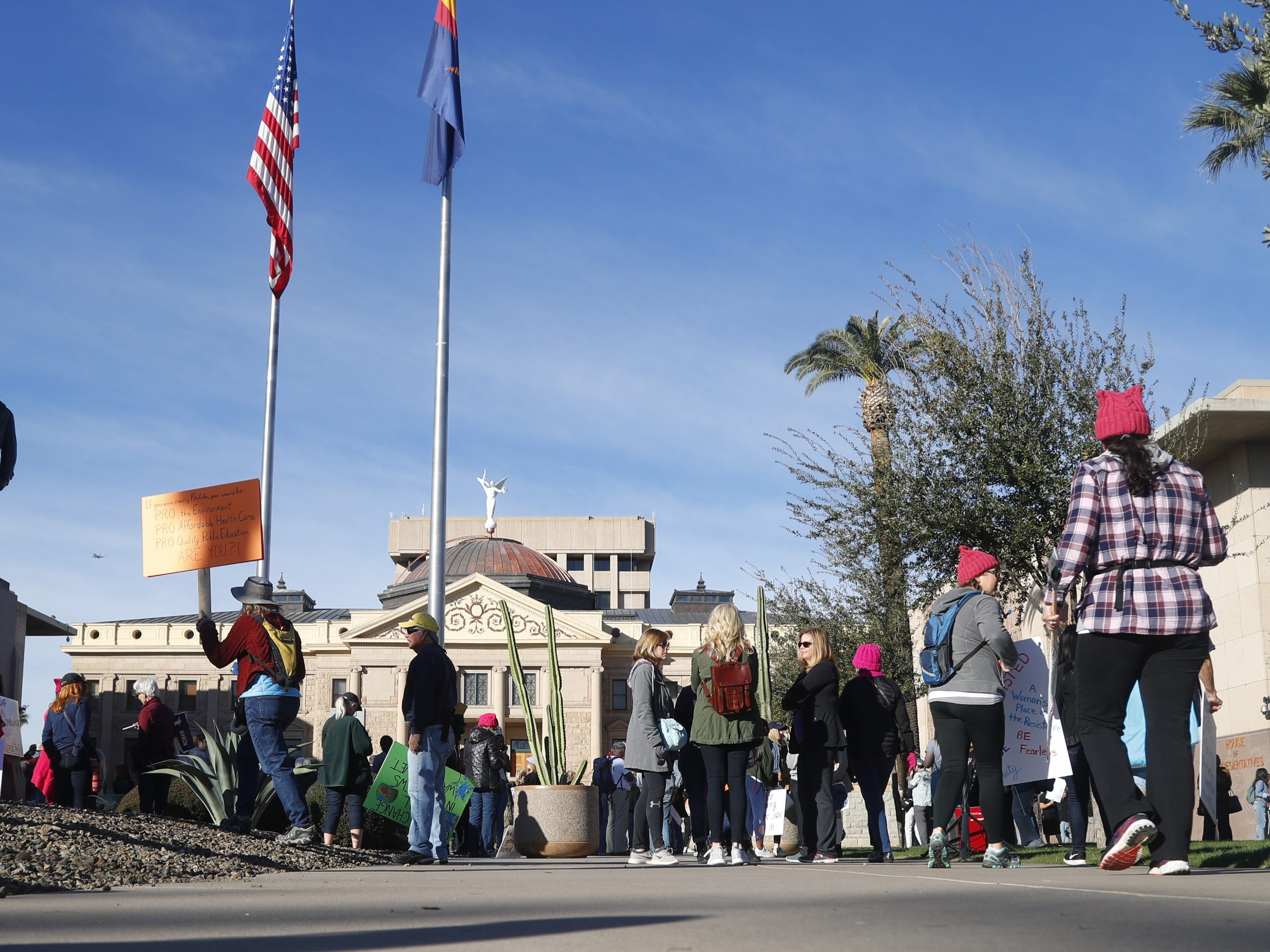 People begin gathering in the morning before the Women's March outside the Arizona Capitol in Phoenix, Jan. 19, 2019.