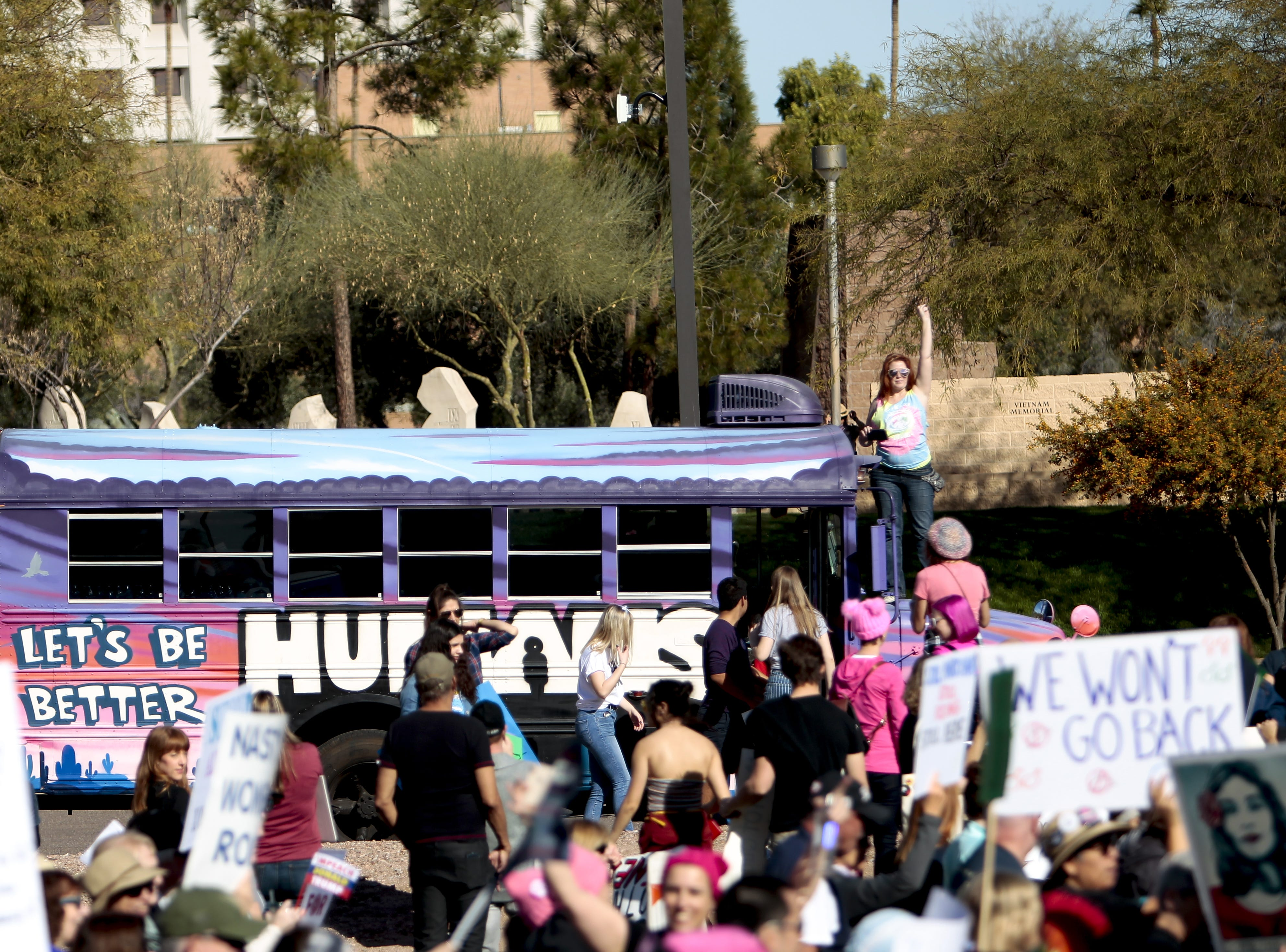 BC Brown waves people over to the Let's Be Better Humans van at the Phoenix Women's March on Jan. 19, 2019, at the Arizona Capitol.