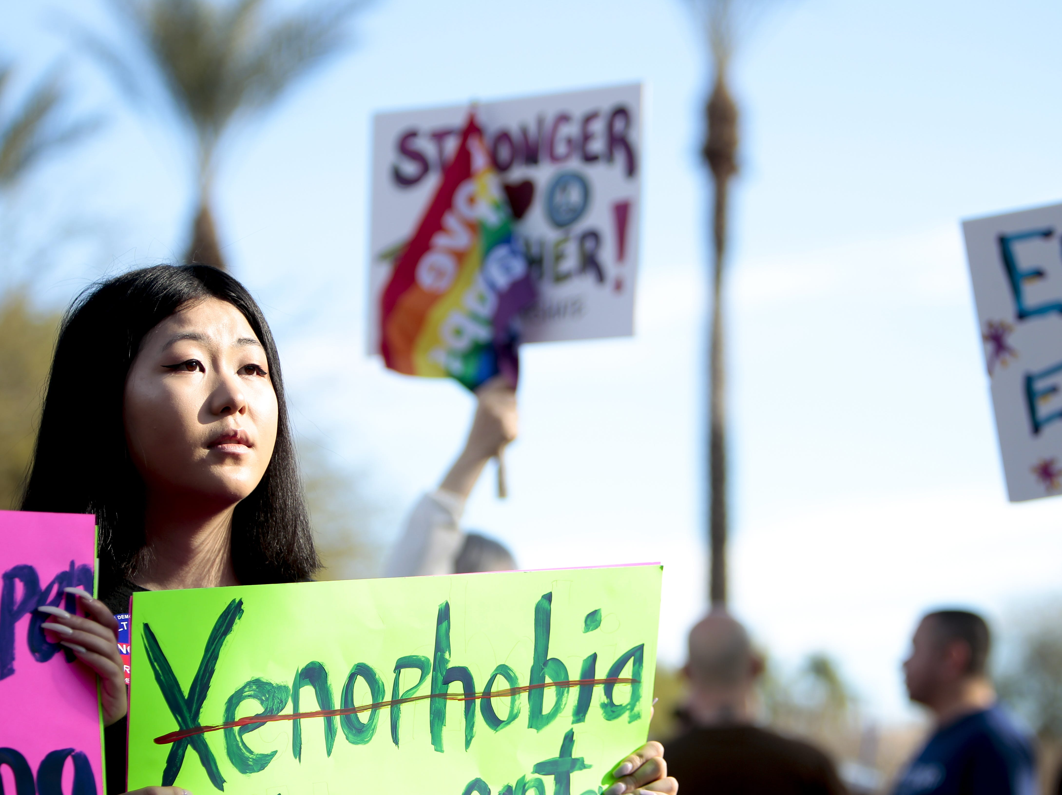 Hunter Lee listens to the speakers as she holds a sign protesting xenophobia at the Phoenix Women's March on Jan. 19, 2019, at the Arizona Capitol.