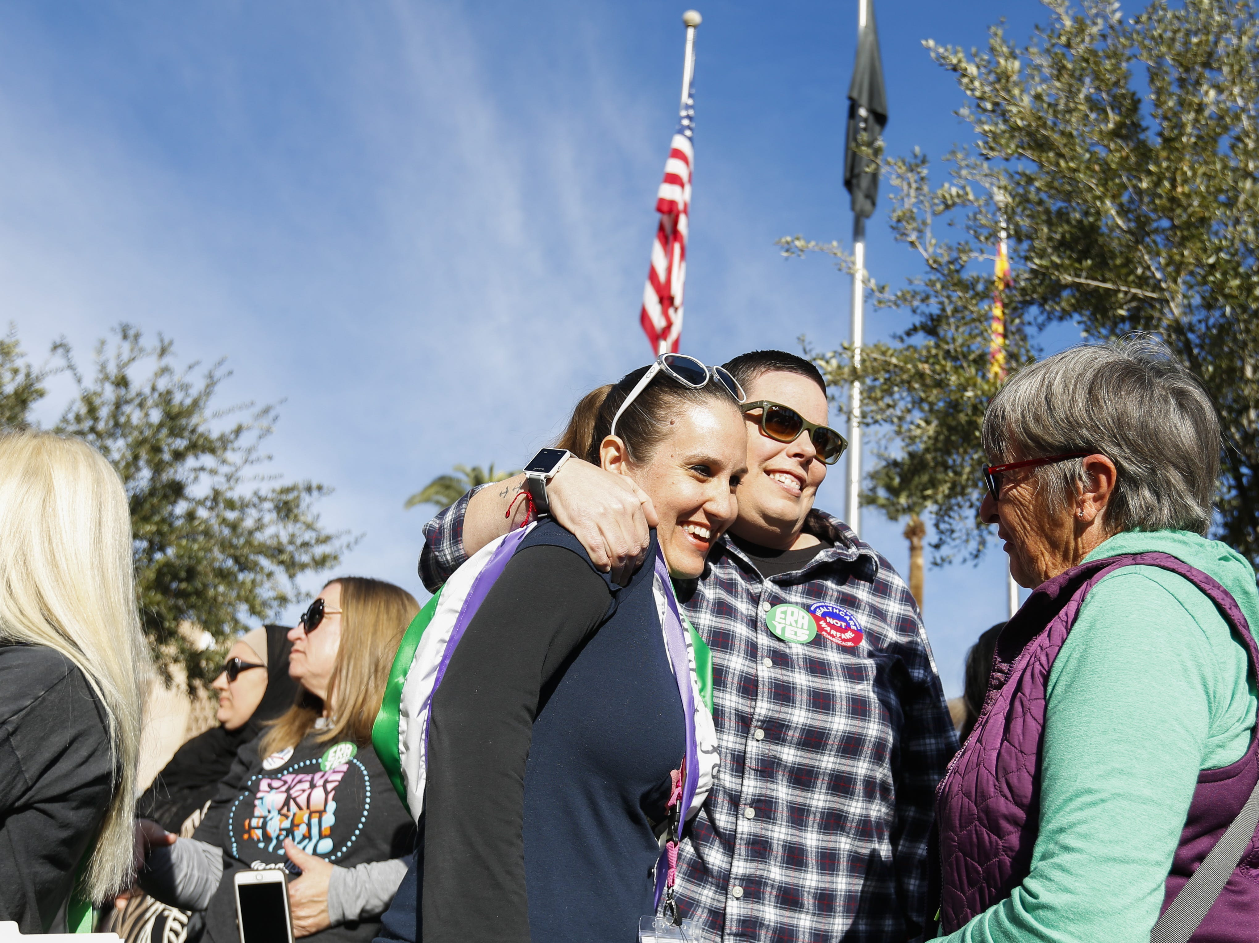 Eva Burch, a lead organizer of the Phoenix Women's March receives a hug after announcing speakers on stage, Jan. 19, 2019.