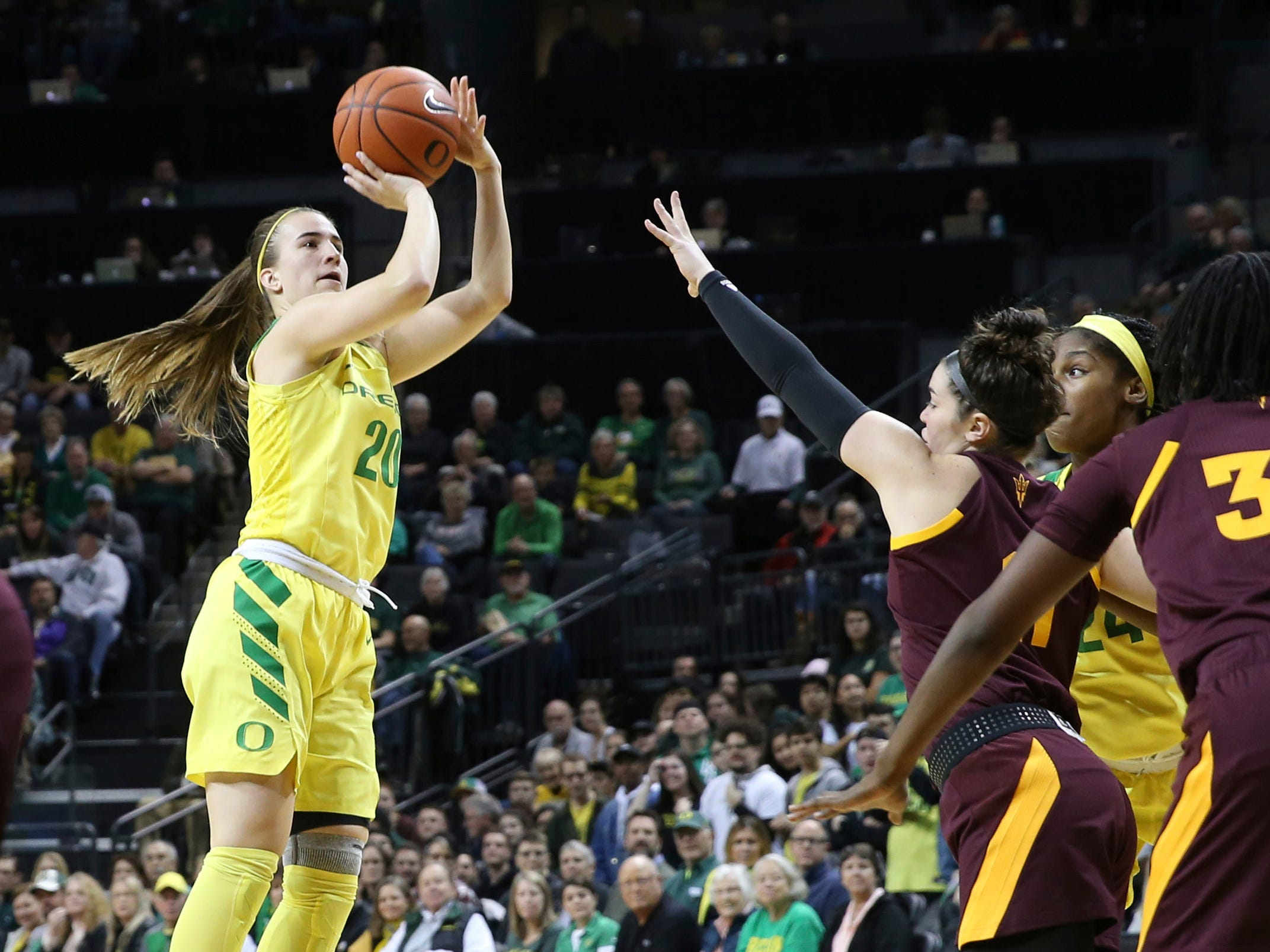 Oregon's Sabrina Ionescu, left, shots over Arizona State's Robbi Ryan, center, and Oregon teammate Ruthy Hebard during the first quarter an NCAA college  basketball game Friday, Jan. 18, 2019, in Eugene, Ore. (AP Photo/Chris Pietsch)