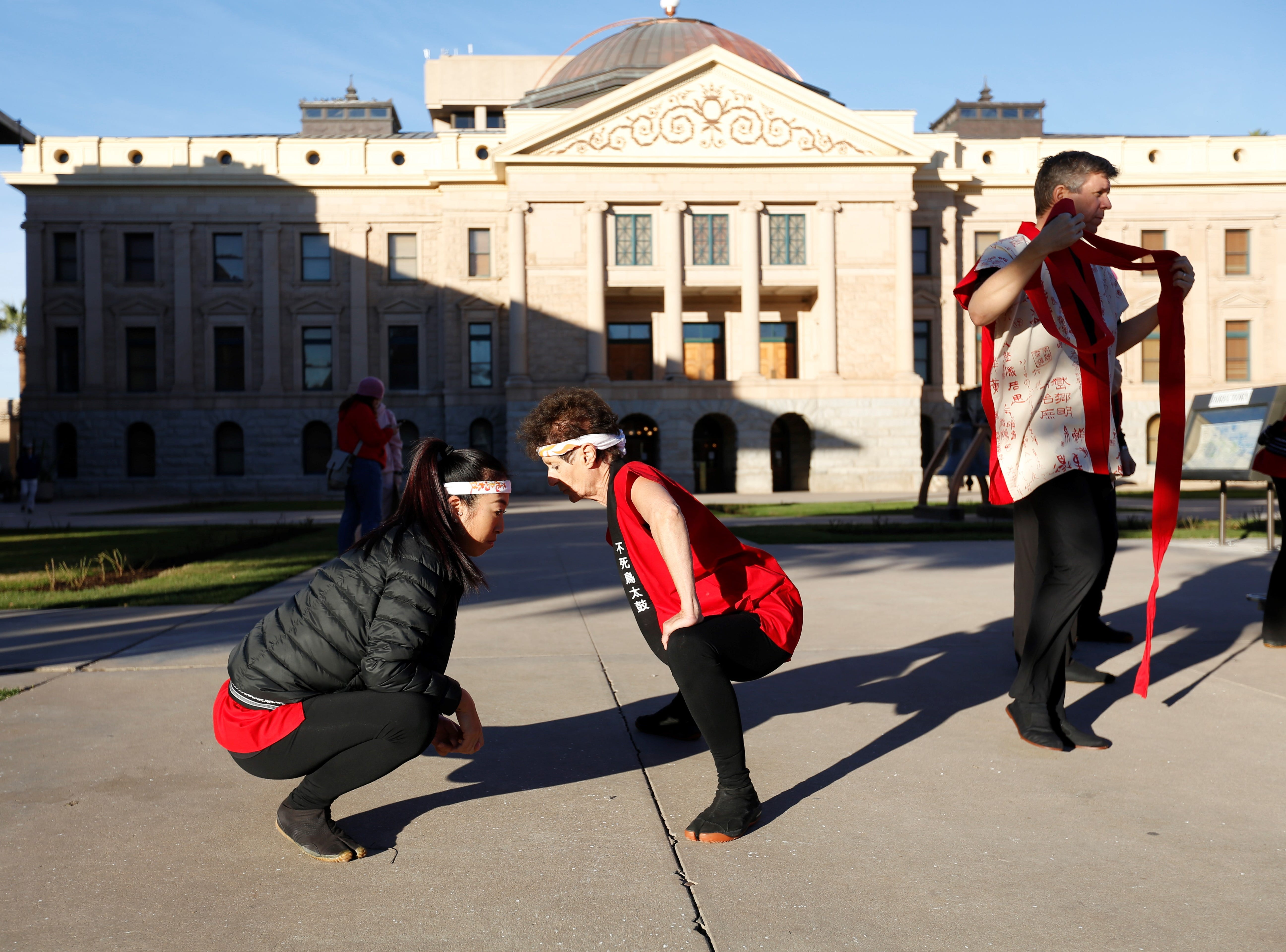Lauren Ellis (left) and Marsha Robb, from the Fushicho Daiko Dojo, stretch before performing Japanese Taiko drumming at the Arizona Capitol, Jan. 19, 2019.