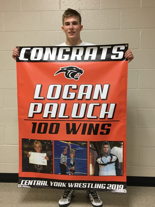Central York senior 126-pounder Logan Paluch poses with a banner commemorating the 100th win of his wrestling career.