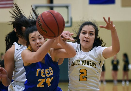 Reed's Tori Baer, left, and Manogue's Lauren Vasquez go after a loose ball on Jan. 8.