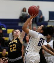 Brockport's Doralis Allen shooting over Athena defender Kathryn Fiannaca (22).