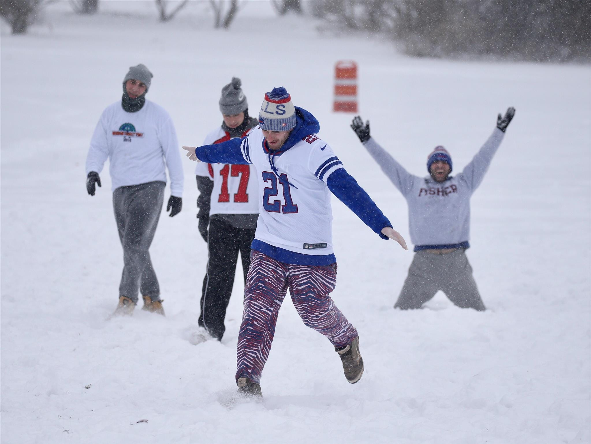 Matt McGillicuddy (21) celebrates a long touchdown catch. A group of friends didn't let the accumulating snow and frigid temperatures dissuade their football game in Cobbs Hill Park.