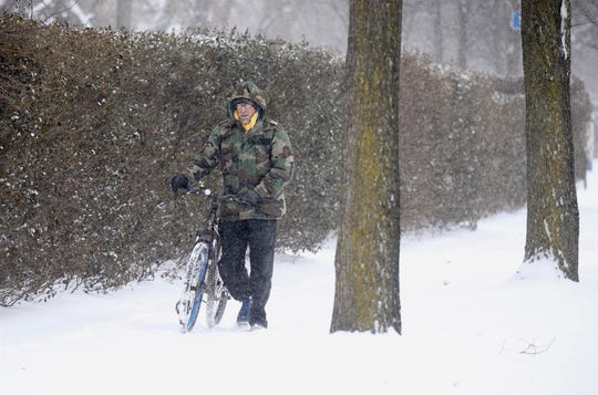 Rick Panipinto of Rochester was forced to push his bike when the snow got too high on the sidewalks along East Ave.